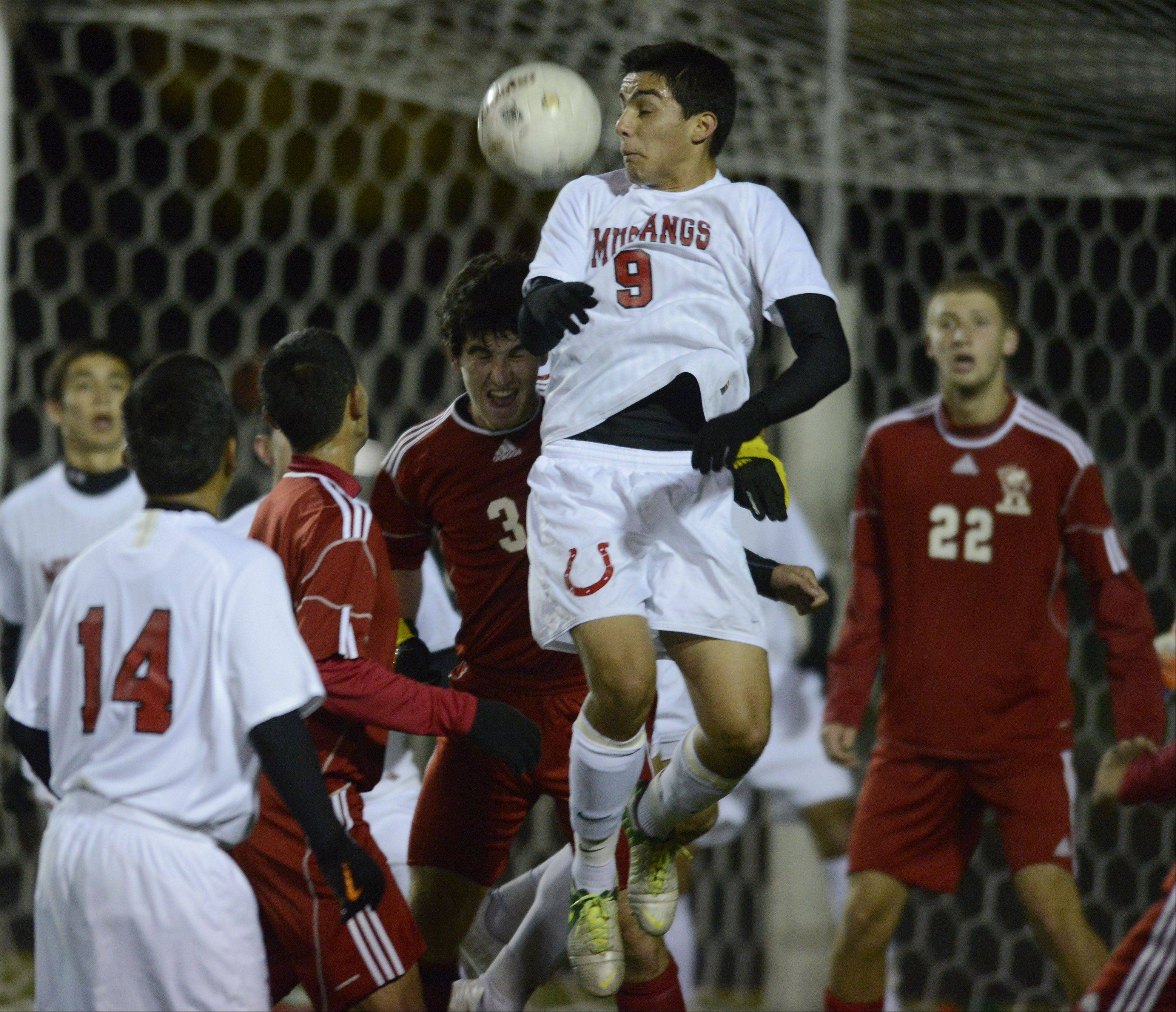 Mundelein's Chuy Alba, middle, tries to get in front of Palatine's Kyle Clancy in an attempt to direct the ball away from his team's goal during Tuesday's game at Palatine.