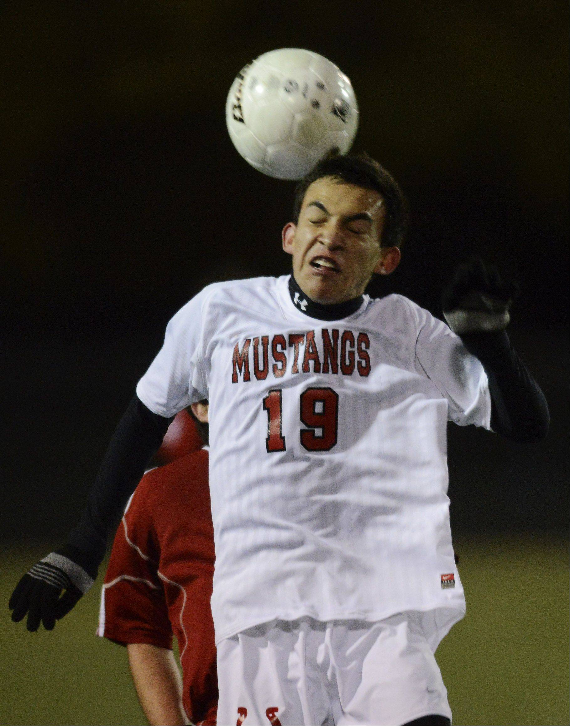 Mundelein's Hector Ruiz leaps for a header during Tuesday's game at Palatine.