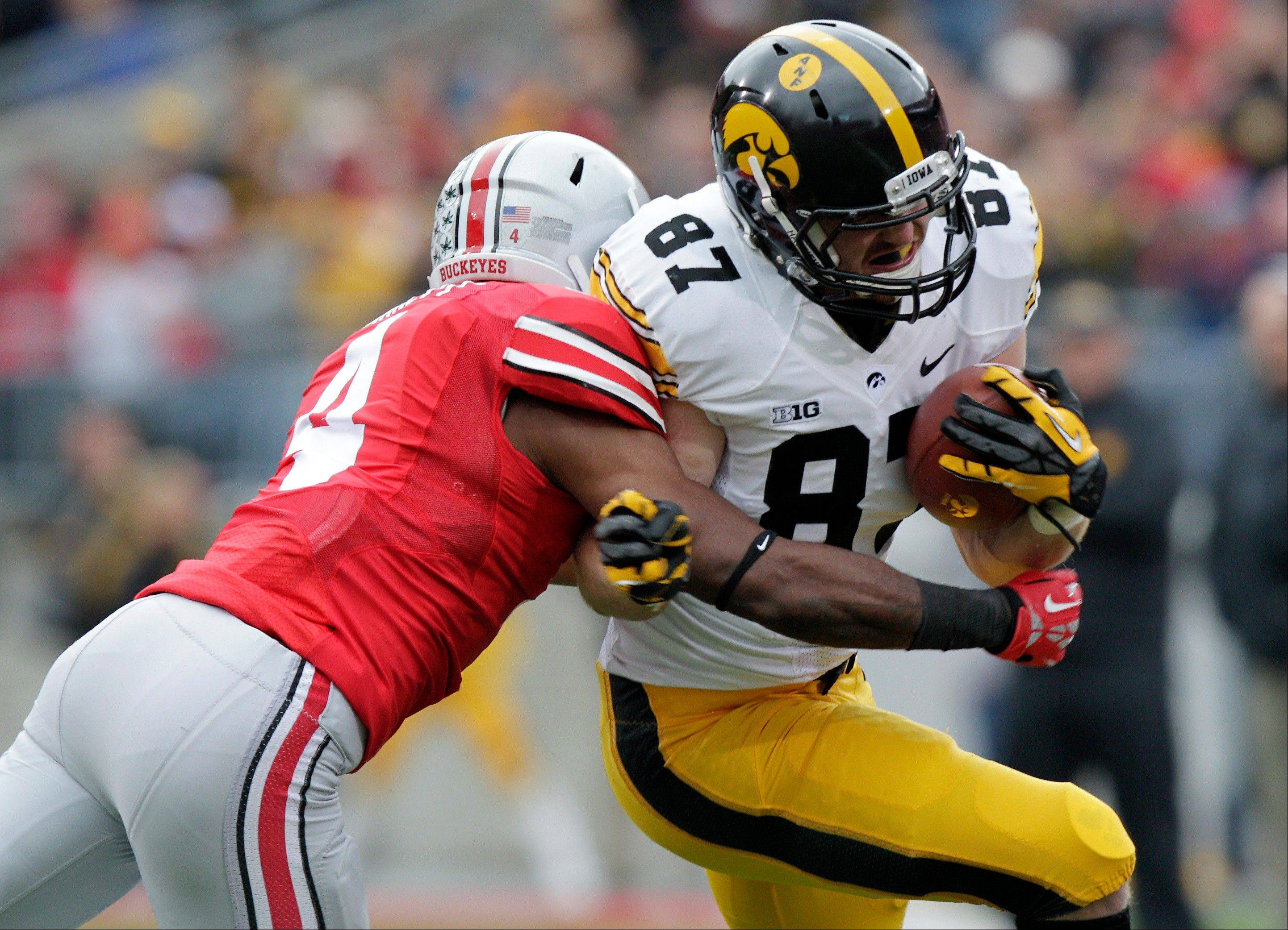 Iowa tight end Jake Duzey, right, tries to get past Ohio State defensive back C.J. Barnett during the first quarter of Saturday's game. Duzey finished with 138 yards, the most for an Iowa tight end in the last 15 seasons.