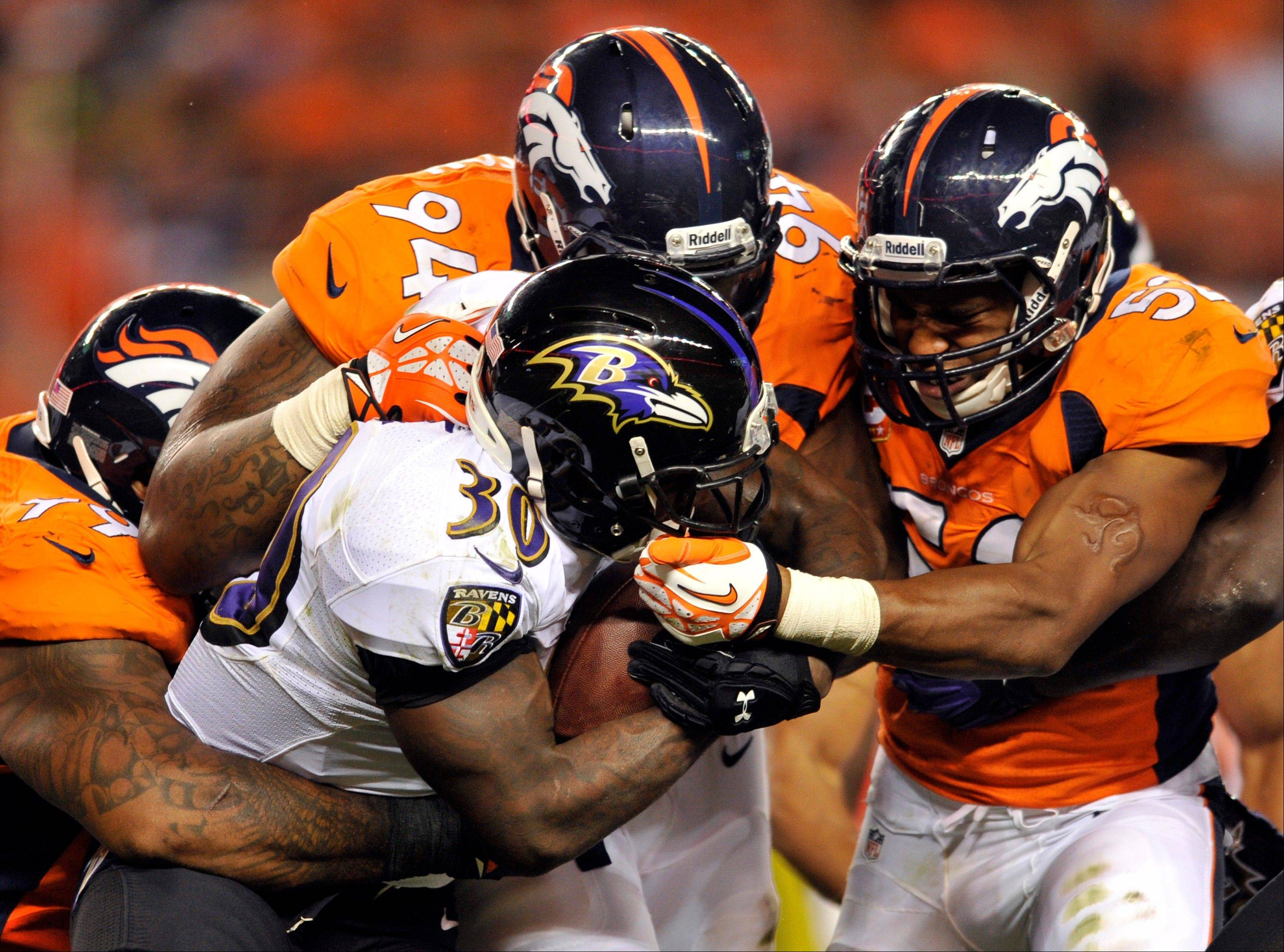 In this Sept. 25, 2013, file photo, Baltimore Ravens running back Bernard Pierce (30) is gang tackled by Denver Broncos defensive tackle Kevin Vickerson (99) , Terrance Knighton (94) and Wesley Woodyard (52) during an NFL football game, in Denver. Increasingly, teams are having trouble getting what they need on the ground on third or fourth down, with 2 or fewer yards needed for a first down or a touchdown. And increasingly, they're trying to pass for those short gains.
