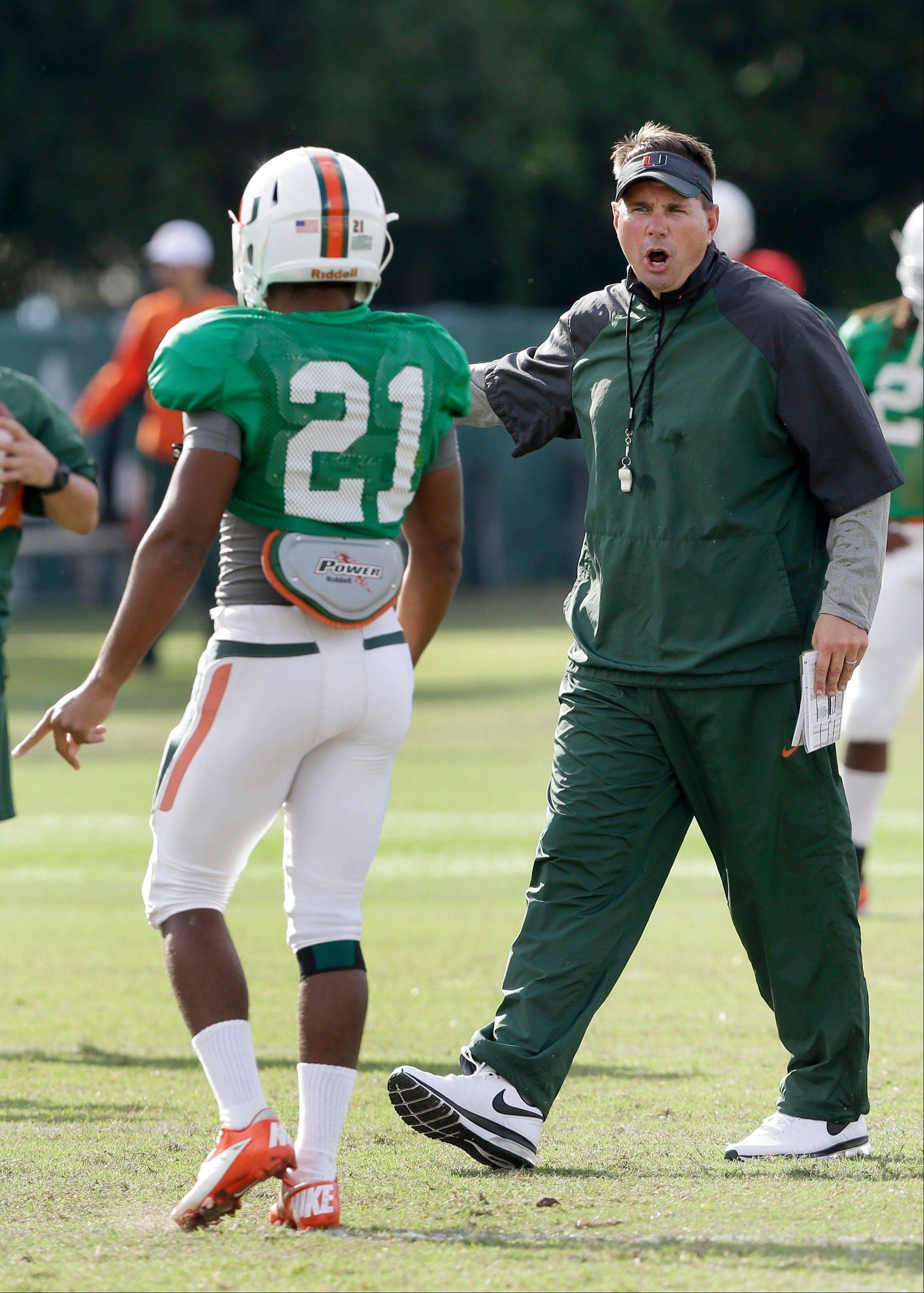 Miami head coach Al Golden, right, talks with defensive back Antonio Crawford during team practice Tuesday, in Coral Gables, Fla. Miami's football team will lose nine scholarships and the men's basketball team will lose three, as part of the penalties the school was handed Tuesday by the NCAA as the Nevin Shapiro scandal presumably drew to a close.