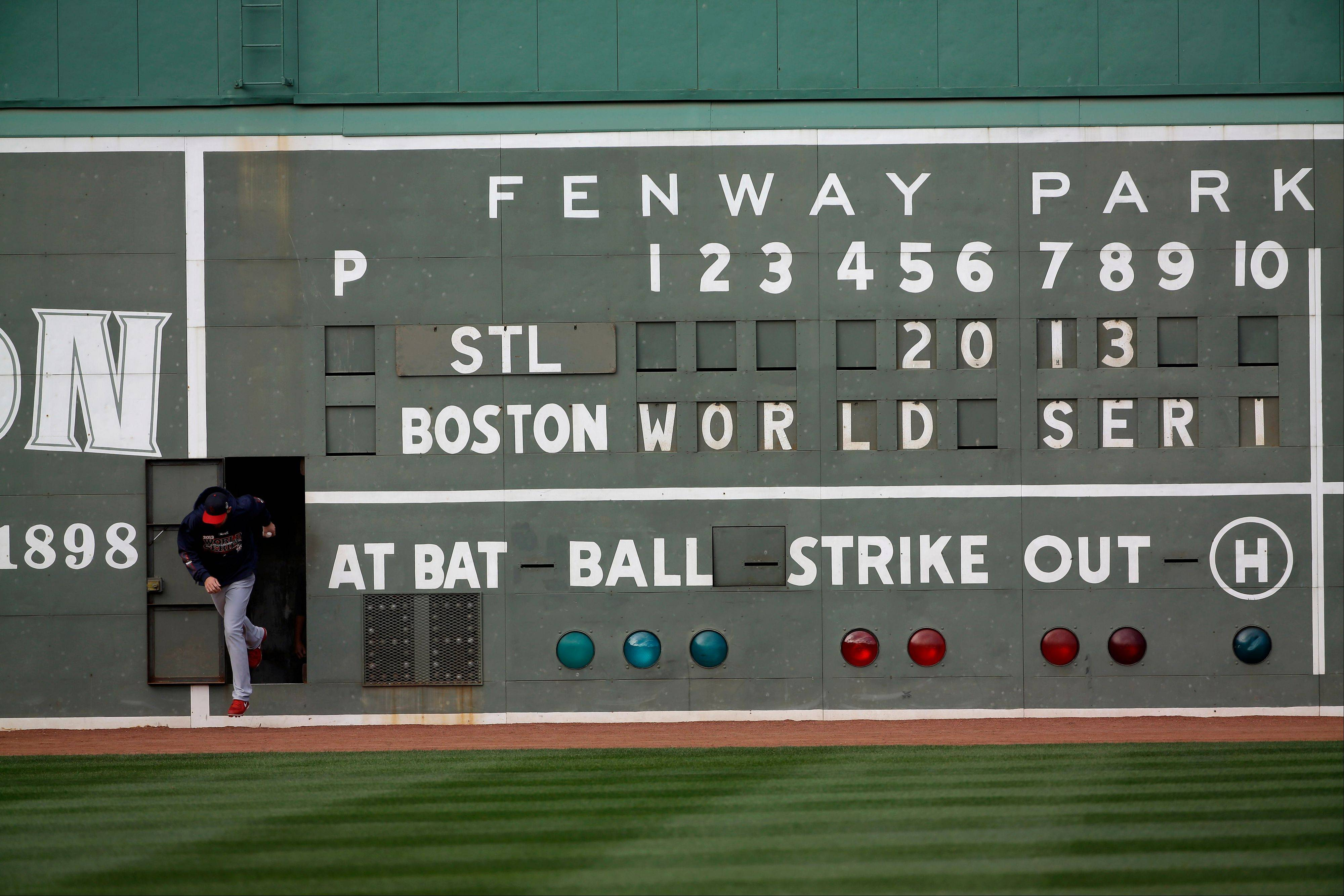 St. Louis Cardinals' Michael Wacha runs out of a scoreboard under the Green Monster before batting practice for Game 1 of baseball's World Series against the Boston Red Sox Tuesday in Boston.