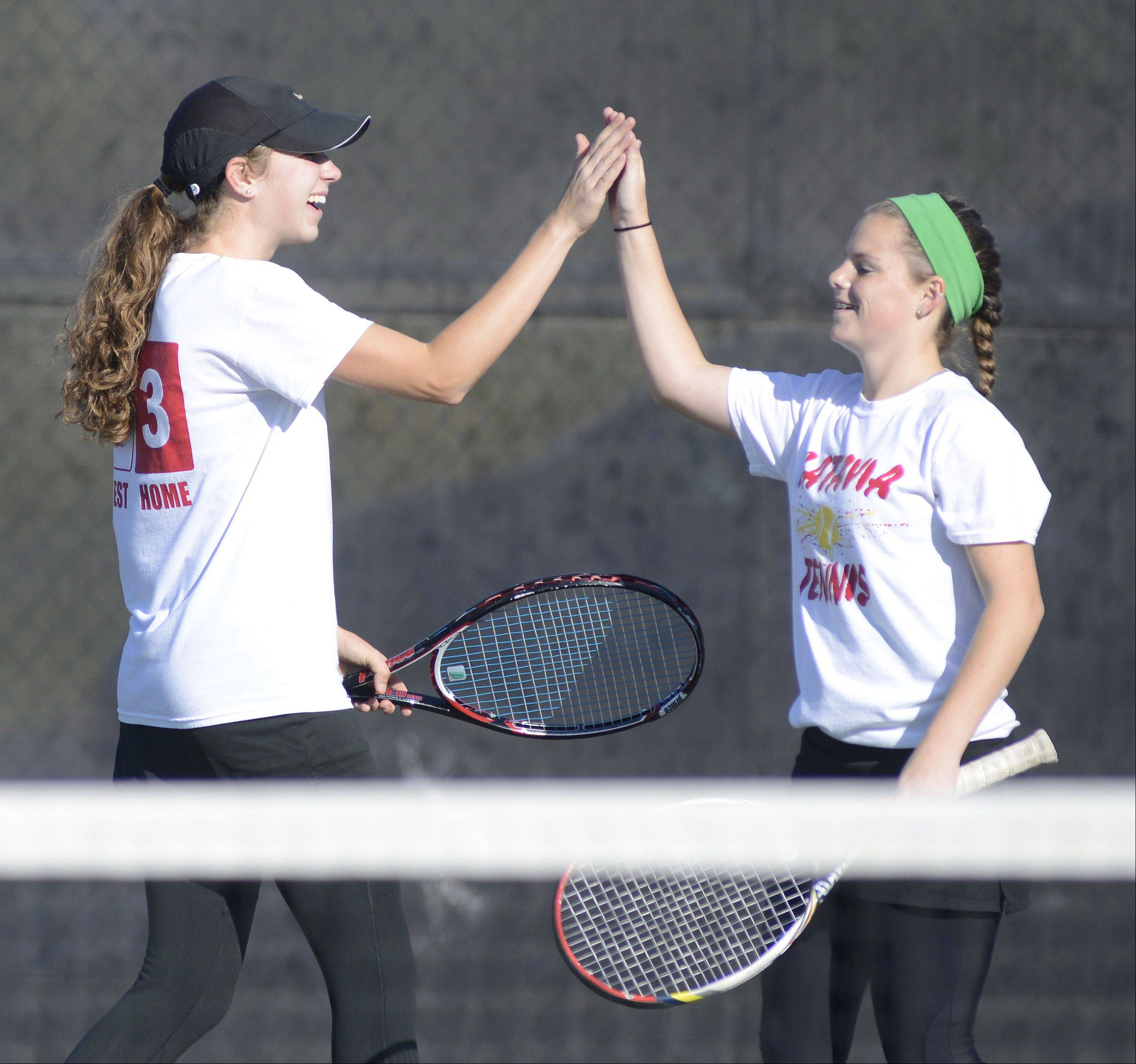 Batavia doubles team Brook LeFevre, left, and Sydney Unterberg celebrate a point over Bartlett during Saturday's sectional tennis meet.