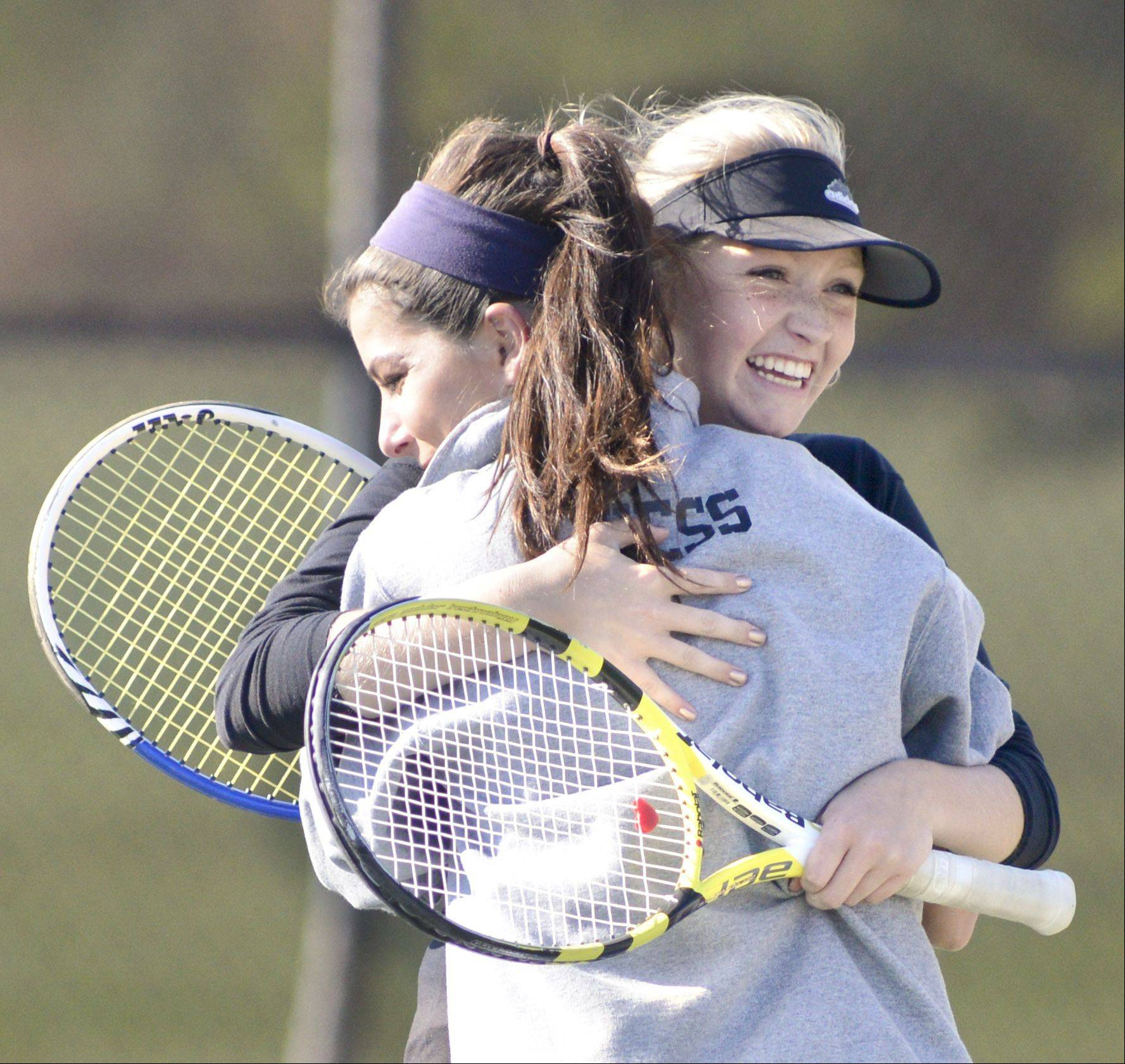 Geneva's Emma Hazel, facing, and Margo Hess embrace after winning their tennis match against St. Charles East during Saturday's sectional meet.
