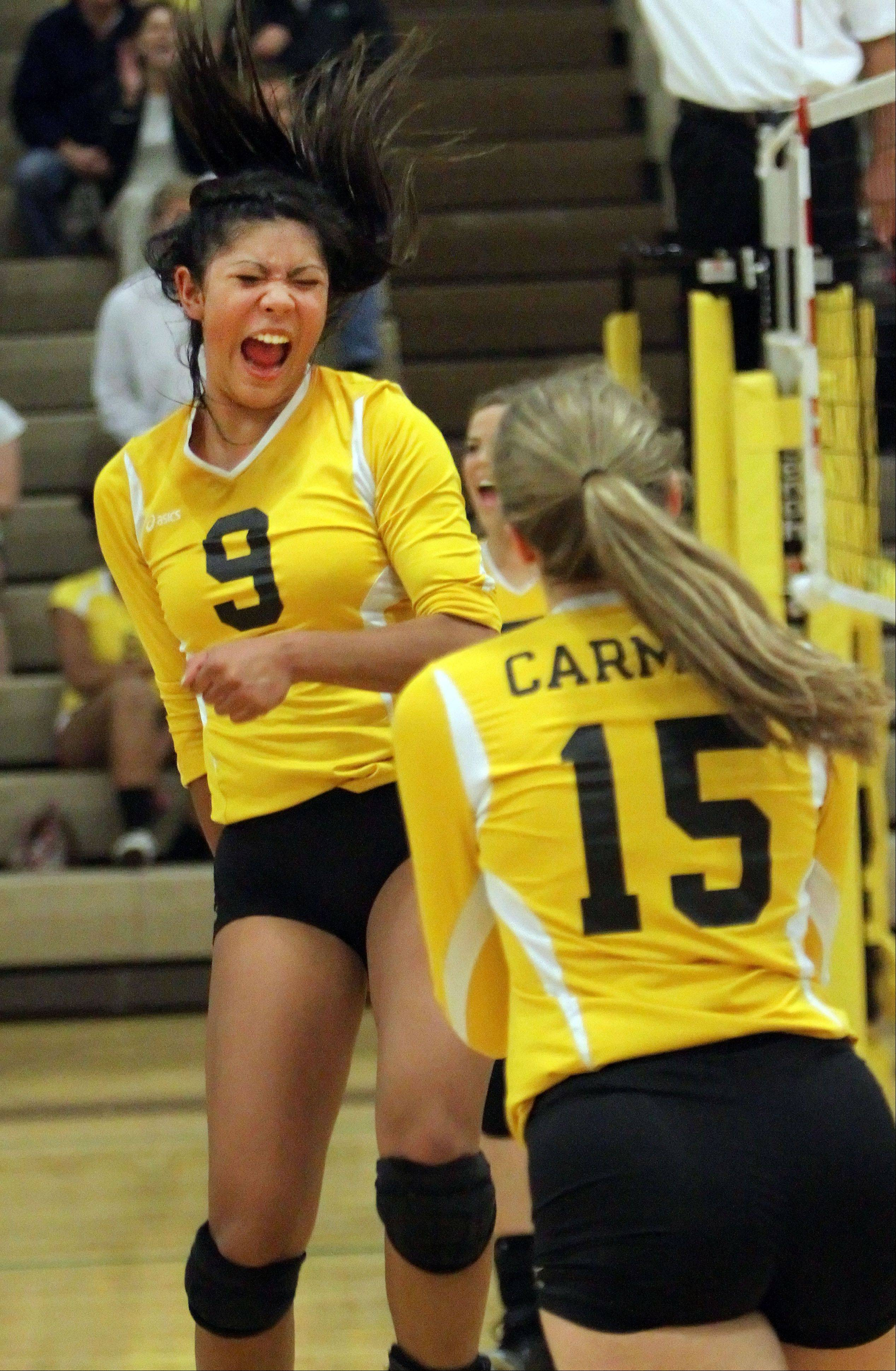 Carmel's Alyssa Armada, left, and Ellie Rengers celebrate after a point against Providence Catholic Tuesday night in Mundelein.