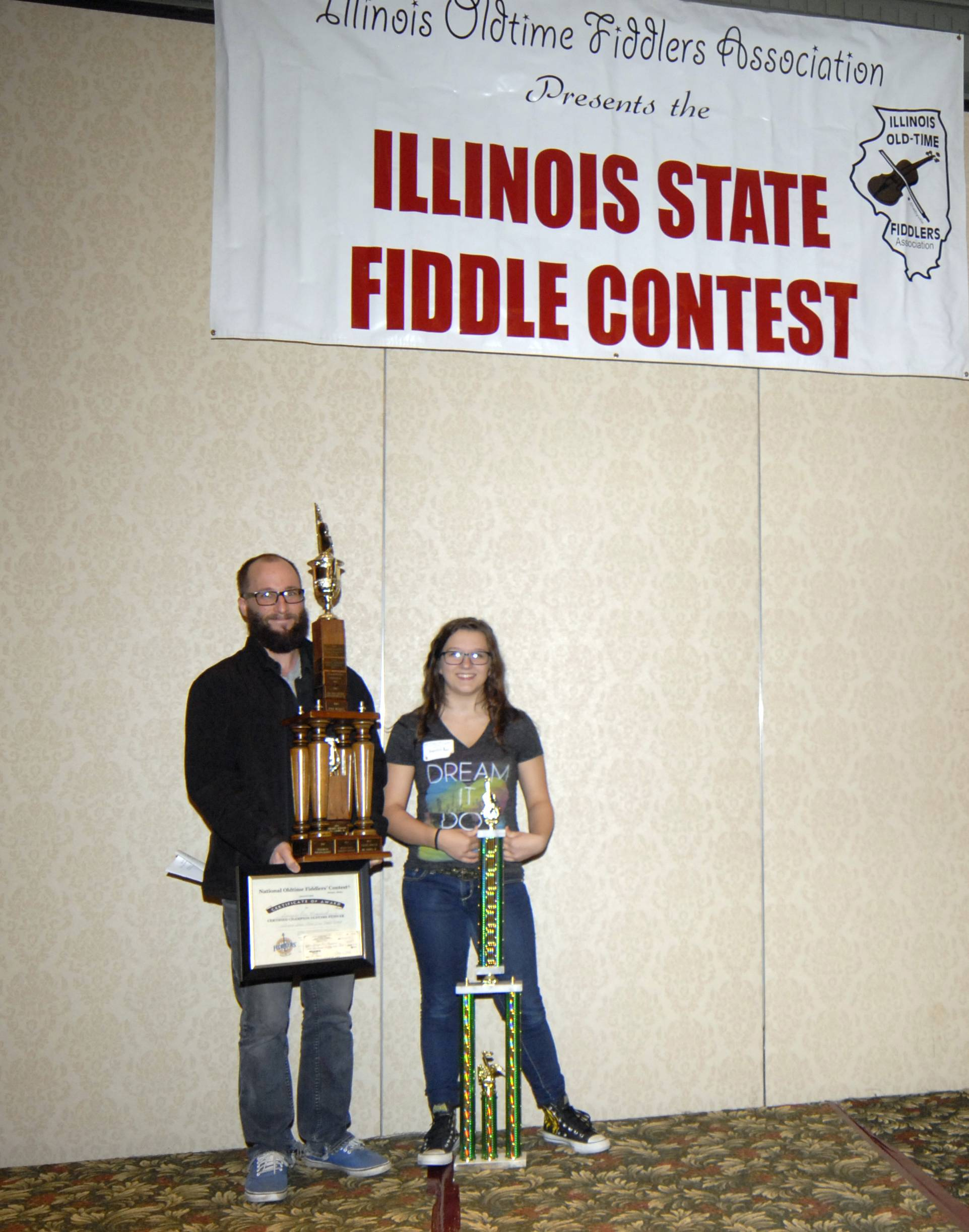 "Fiddle teacher Shawn Drake (L) helps hold Georgia Rae Mussared's (R) trophies and awards she won at the Illinois State Old Time Fiddler's Contest in Effingham, IL, where she was named the 2013 Grand Champion. The win sends her to the Grand National Old Time Fiddlers Contest in Weiser, Idaho in June. The ""Weiser"" is one of the most prestigious flddle contests in the nation."