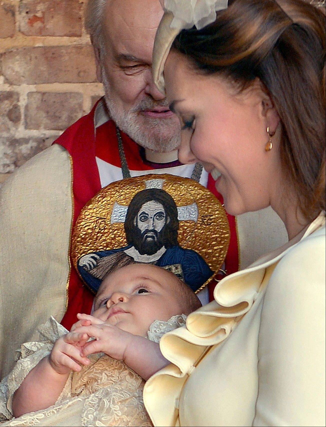 Kate Duchess of Cambridge carries her son Prince George after his christening Wednesday at the Chapel Royal in St James' Palace in London, with the Bishop of London Richard Chartres behind. The prince was christened Wednesday with water from the River Jordan at a rare four-generation gathering of the royal family in London.