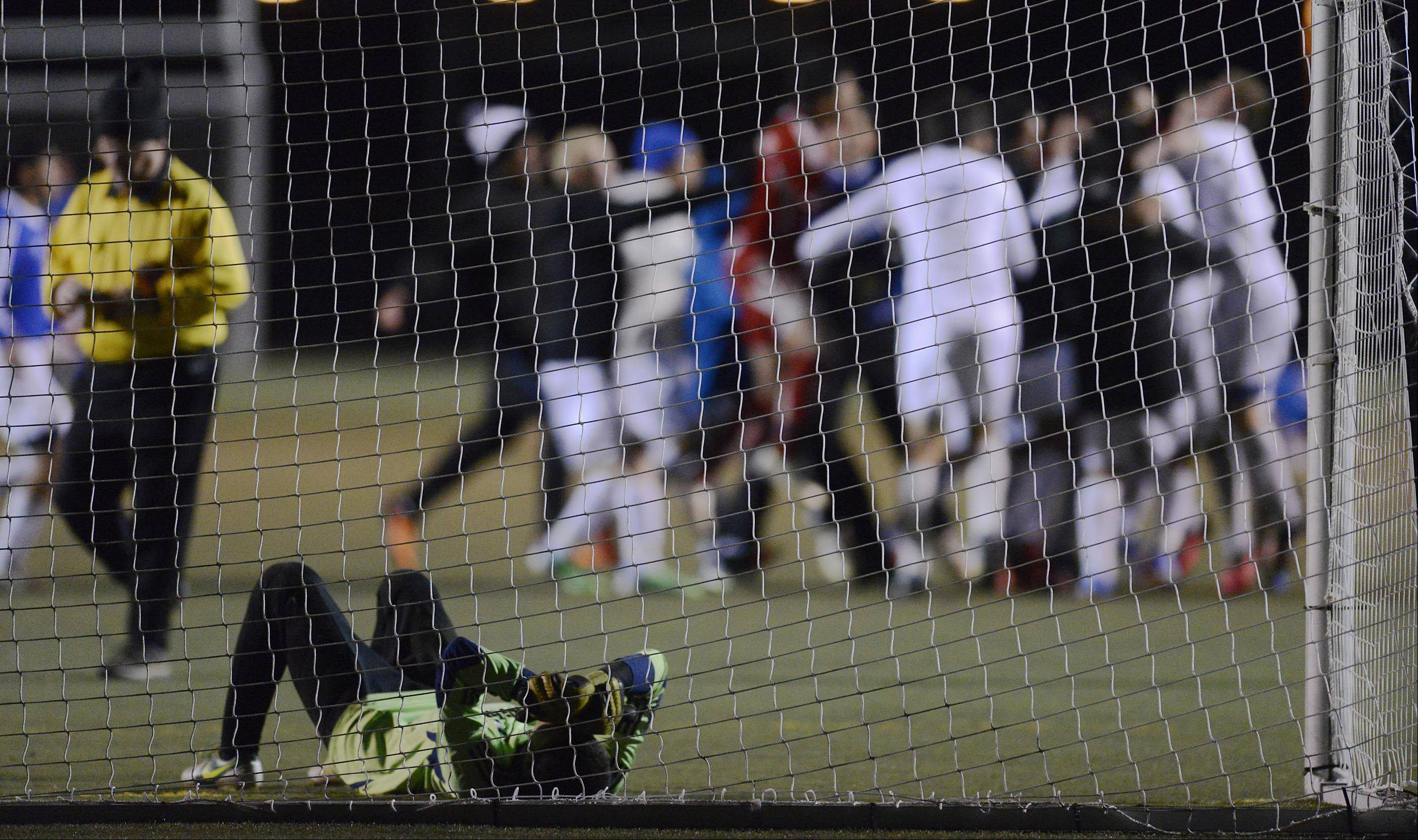 Dundee-Crown goalkeeper Jose Gonzalez covers his eyes as Larkin celebrates its 4-2 shootout win Wednesday at Millennium Field in Streamwood.