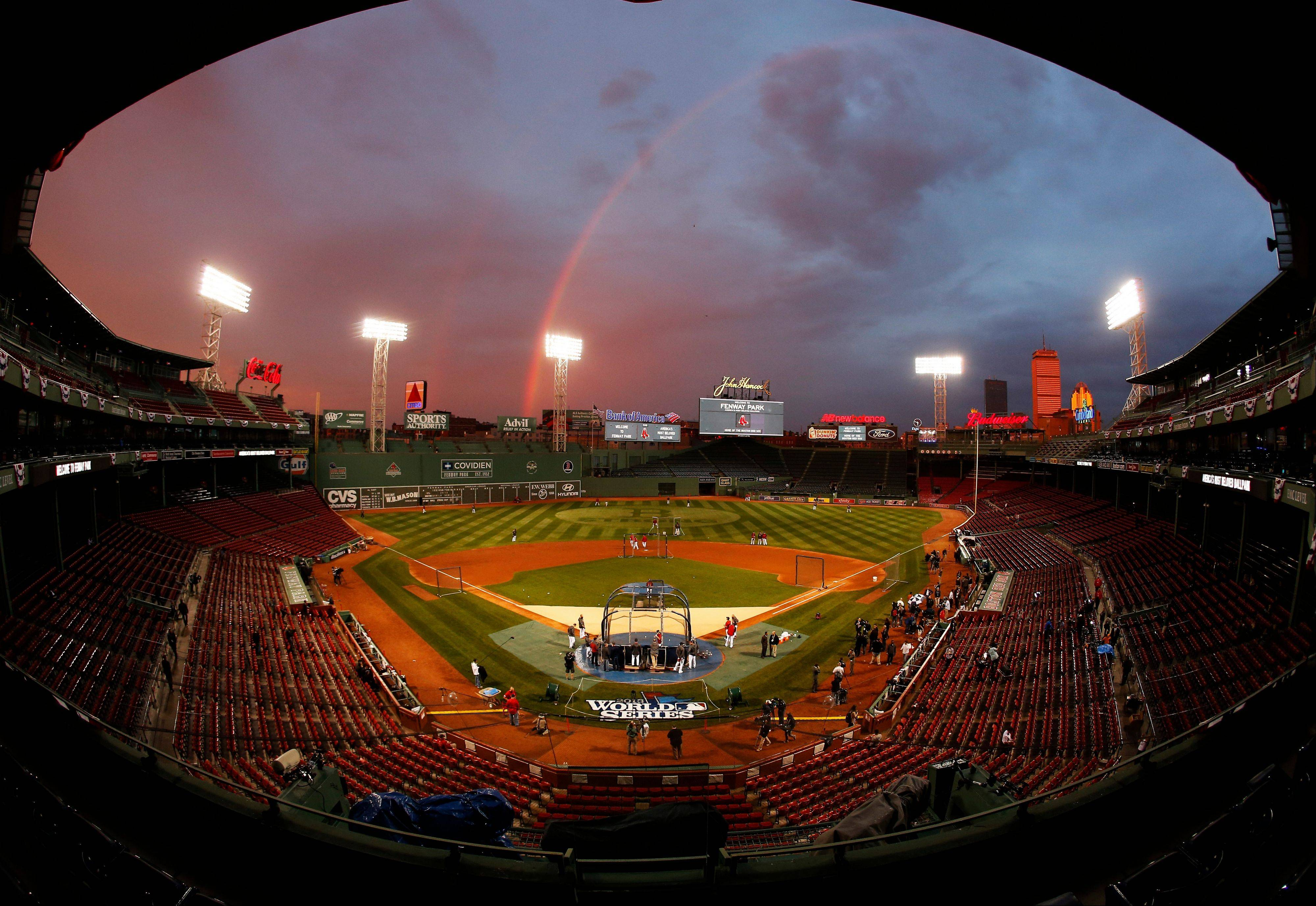 Ithis image taken with a fisheye lens, Boston Red Sox players take batting practice as a rainbow appears in the sky above Fenway Park Tuesday in Boston. The Red Sox are scheduled to host the St. Louis Cardinals in Game 1 of baseball's World Series on Wednesday.