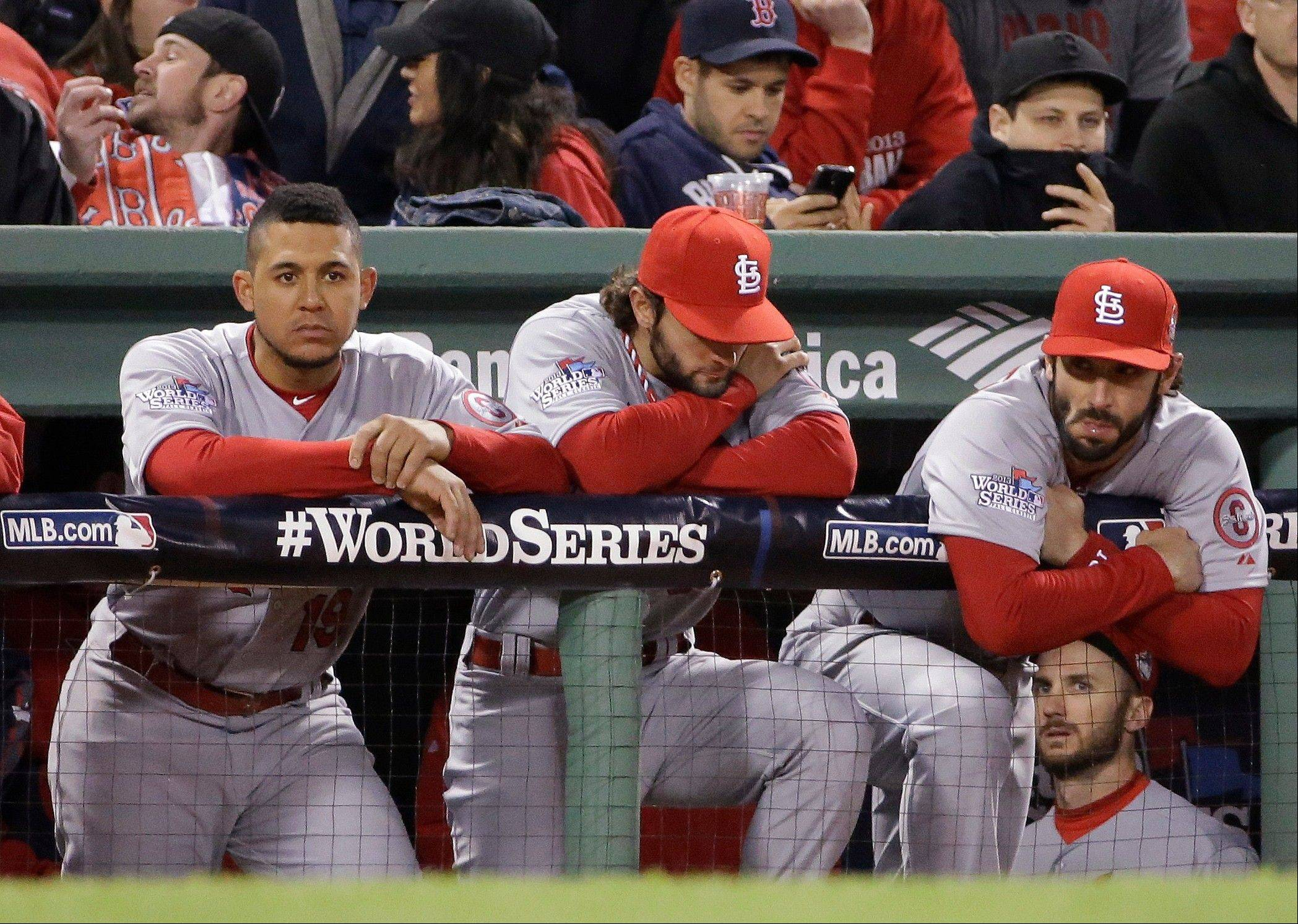 St. Louis Cardinals from left, Jon Jay, Pete Kozma and Matt Carpenter watch from the dugout during the ninth inning Wednesday of Game 1 of baseball's World Series against the Boston Red Sox in Boston. The Red Sox won 8-1.