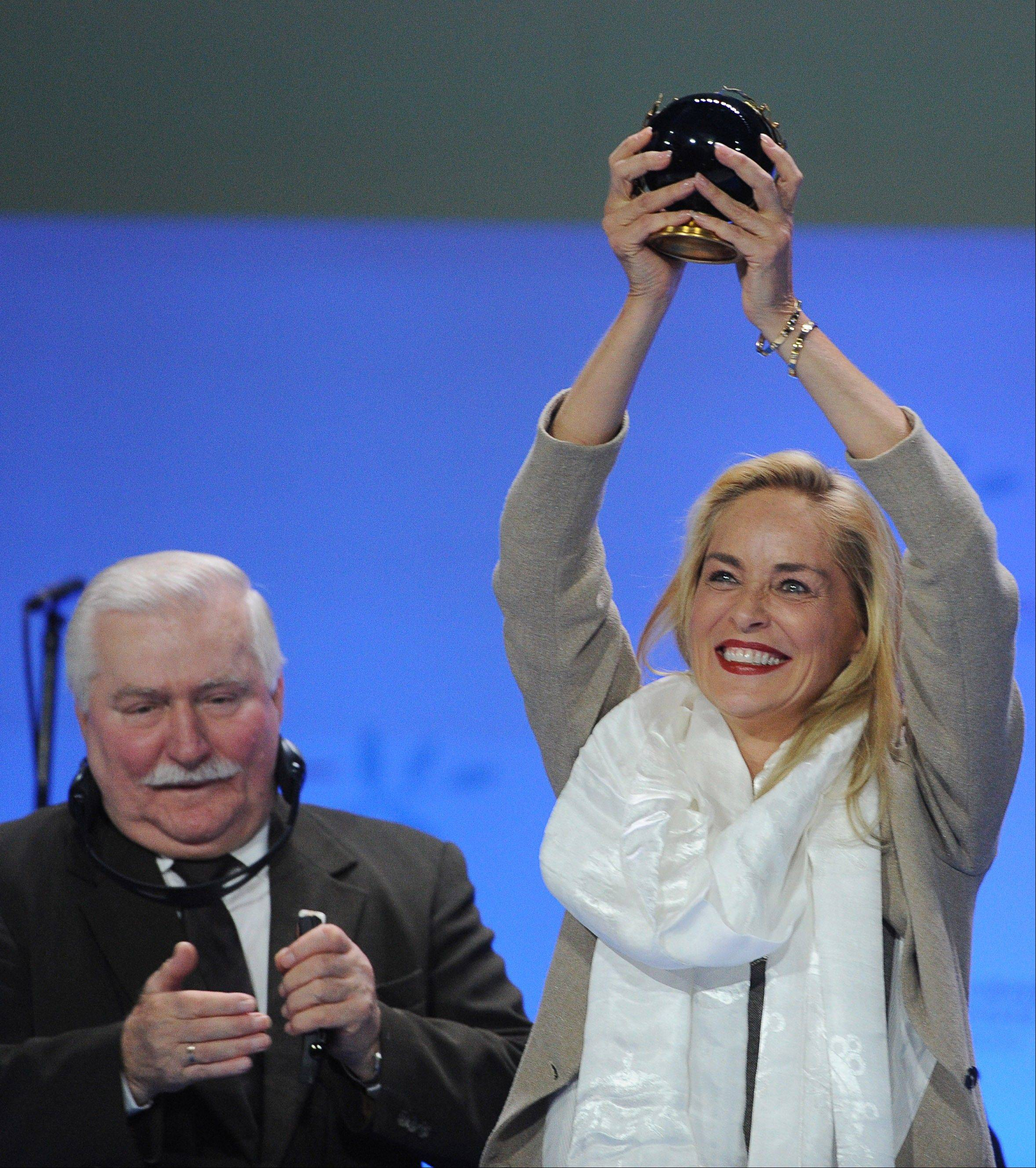Actress Sharon Stone raises the Summit's Peace Prize she just received Wednesday from Nobel Peace laureates, as former Polish President Lech Walesa applauds during the award receiving ceremony in Warsaw, Poland. Stone was awarded with the prize in recognition of her activities against HIV and AIDS.