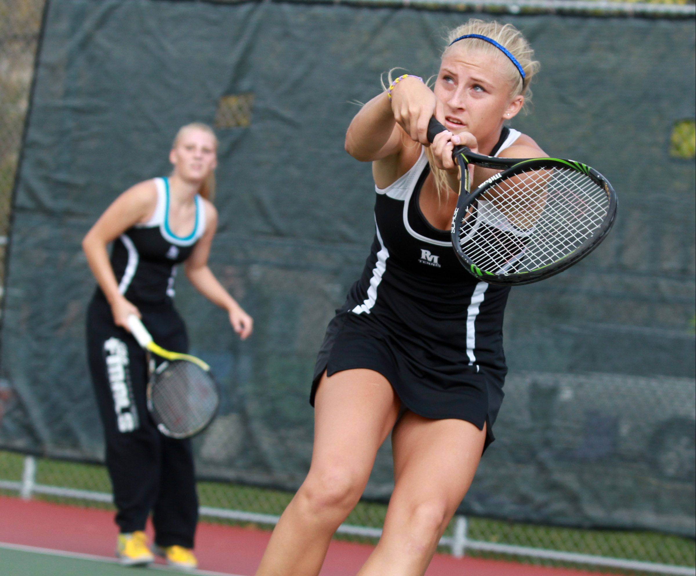 Rolling Meadows' Jackie Kemph swings at the ball while teaming up with sister Allie on their way to a victory in the Mid-Suburban League championship match at first doubles.