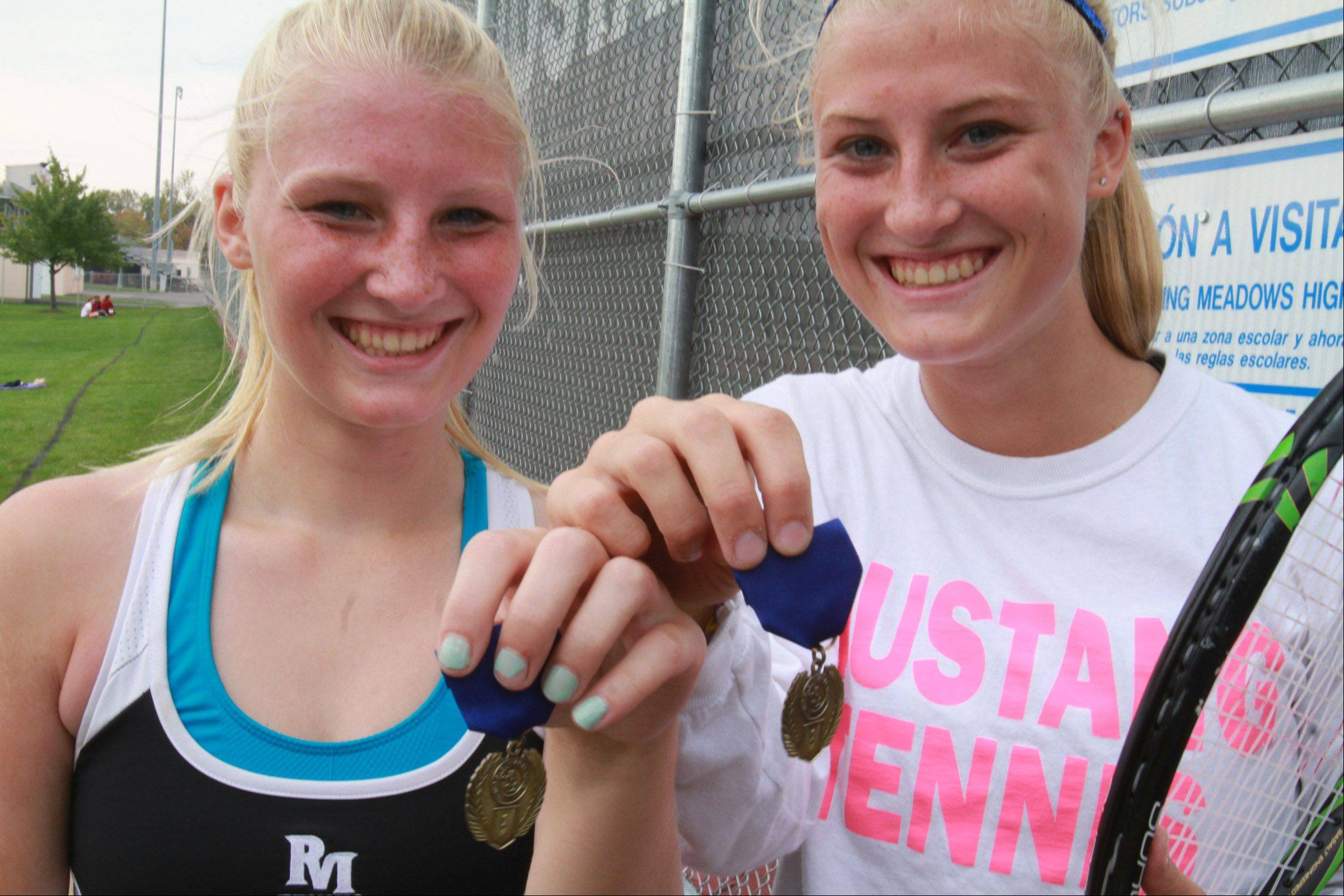 Rolling Meadows' Jackie, left, and Allie Kemph savor their MSL victory at first doubles on their home courts earlier this month.