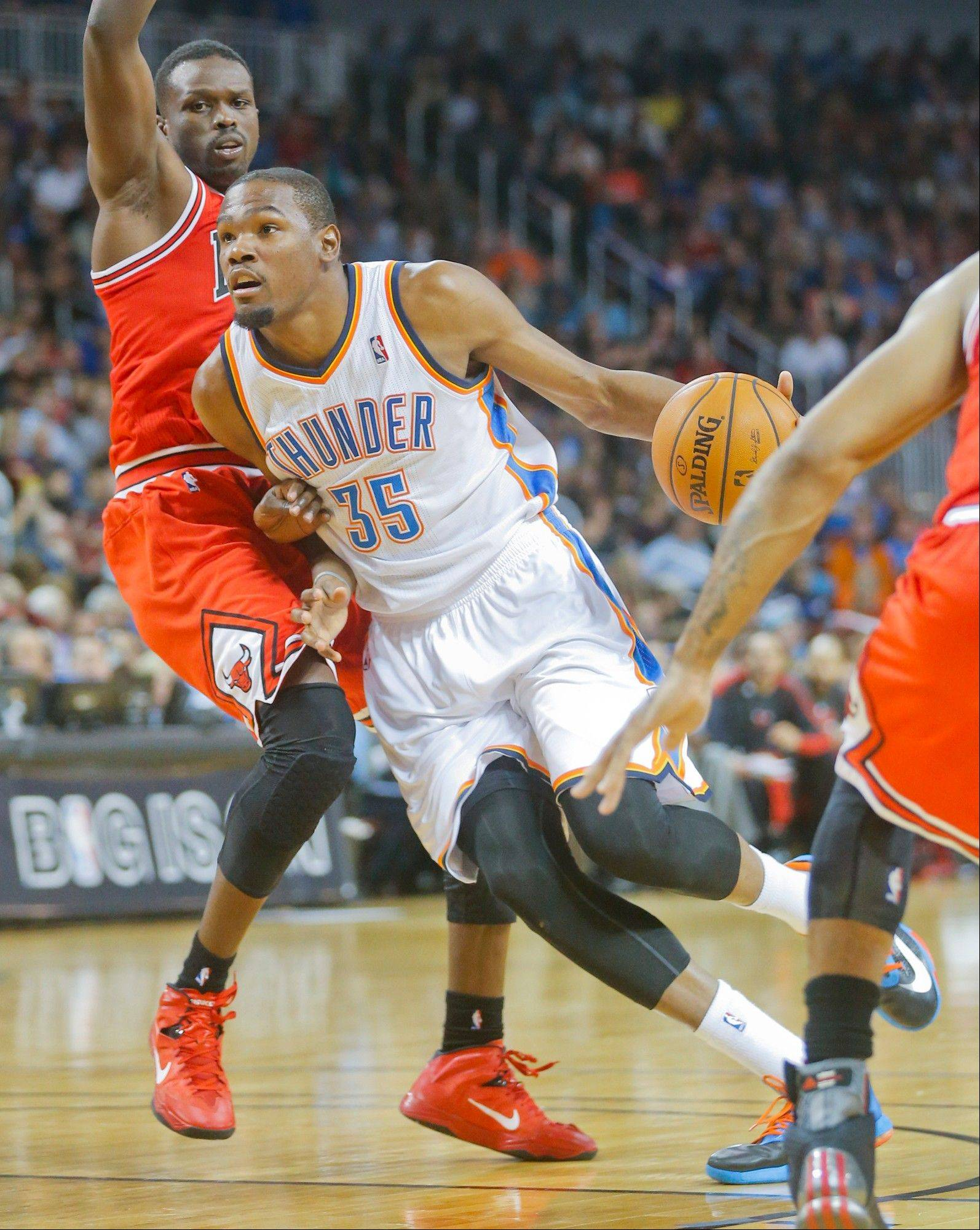 Oklahoma City's Kevin Durant heads to the basket against the Bulls' Luol Deng in the second quarter during Wednesday night's preseason game in Wichita, Kan.