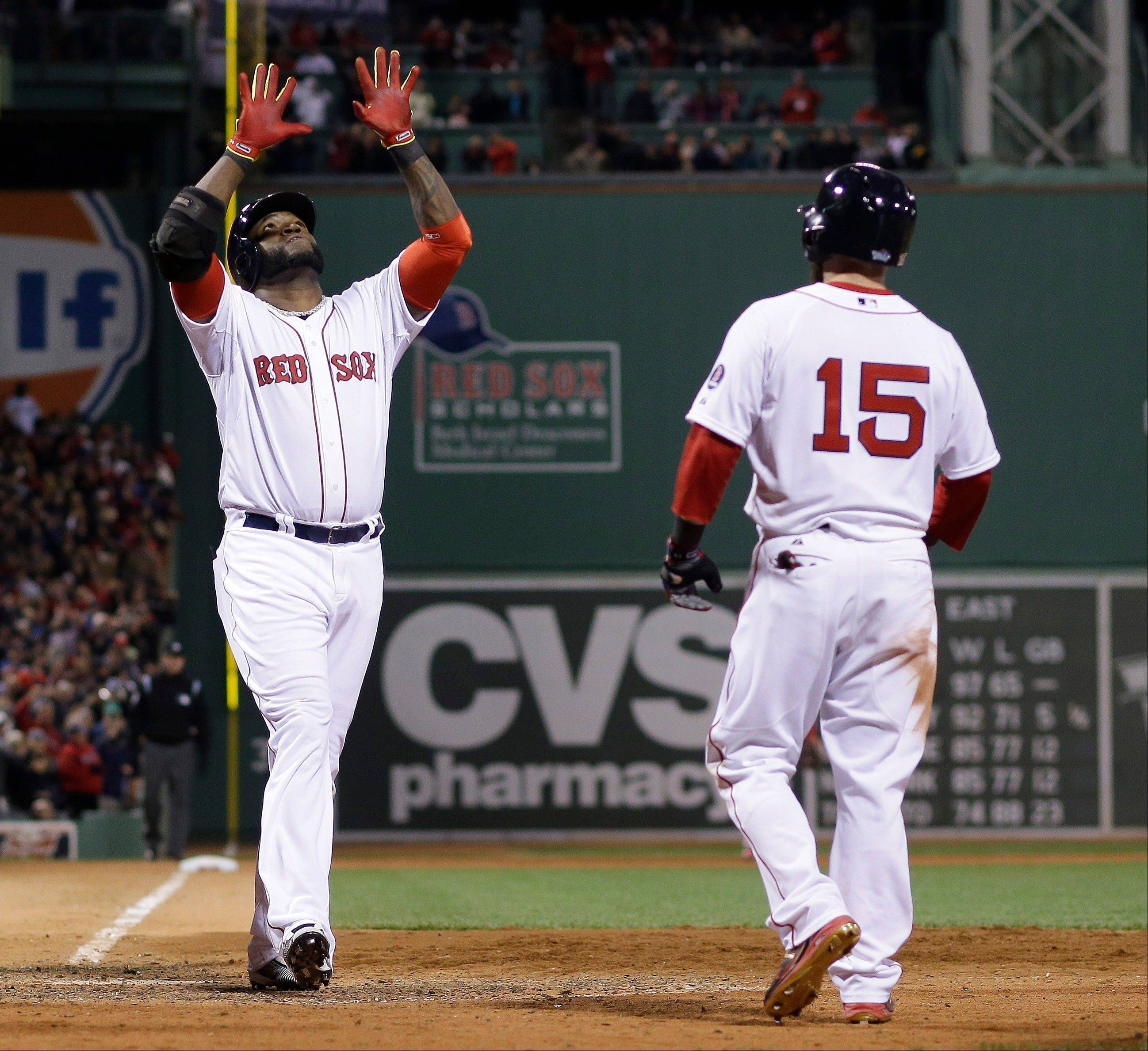 Boston Red Sox's David Ortiz celebrates as he crosses home after hitting a two-run home run Wednesday during the seventh inning of Game 1 of baseball's World Series against the St. Louis Cardinals in Boston. Dustin Pedroia (15) scored on the homer.