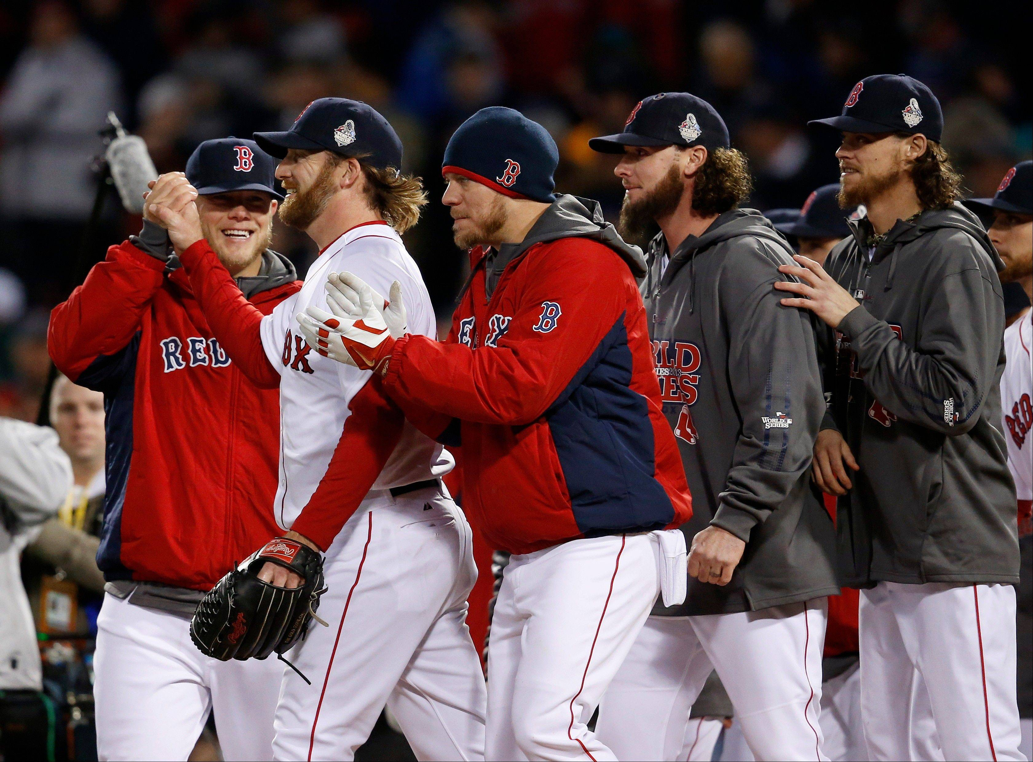 Boston Red Sox relief pitcher Ryan Dempster, second from left, is congratulated by teammates after the Red Sox defeated the St. Louis Cardinals, 8-1 Wednesday night in Game 1 of baseball's World Series in Boston.