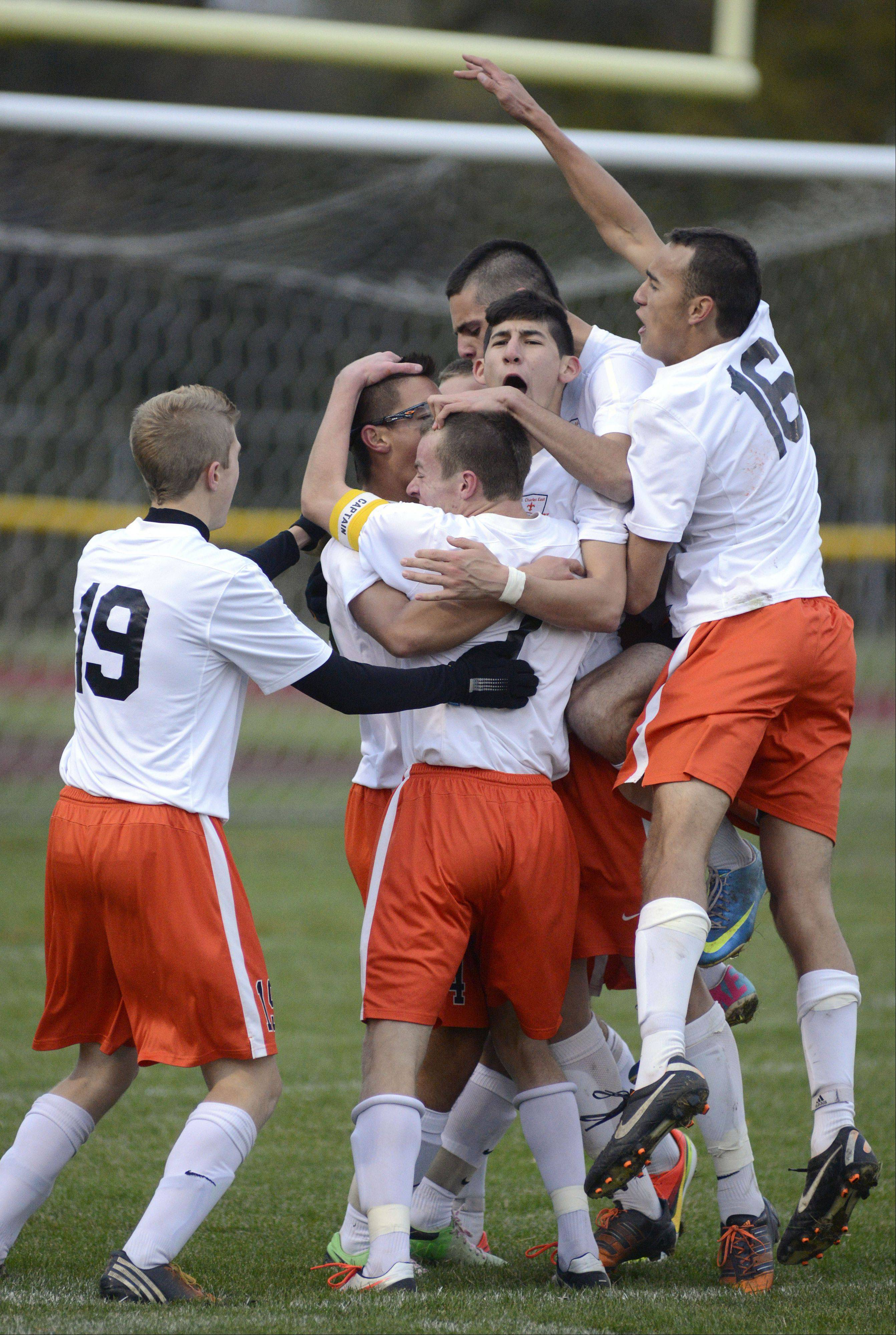 St. Charles East's Zach Manibog (center, with glasses) is swarmed by teammates after scoring the first goal for the Saints in the second half on Wednesday, October 23.