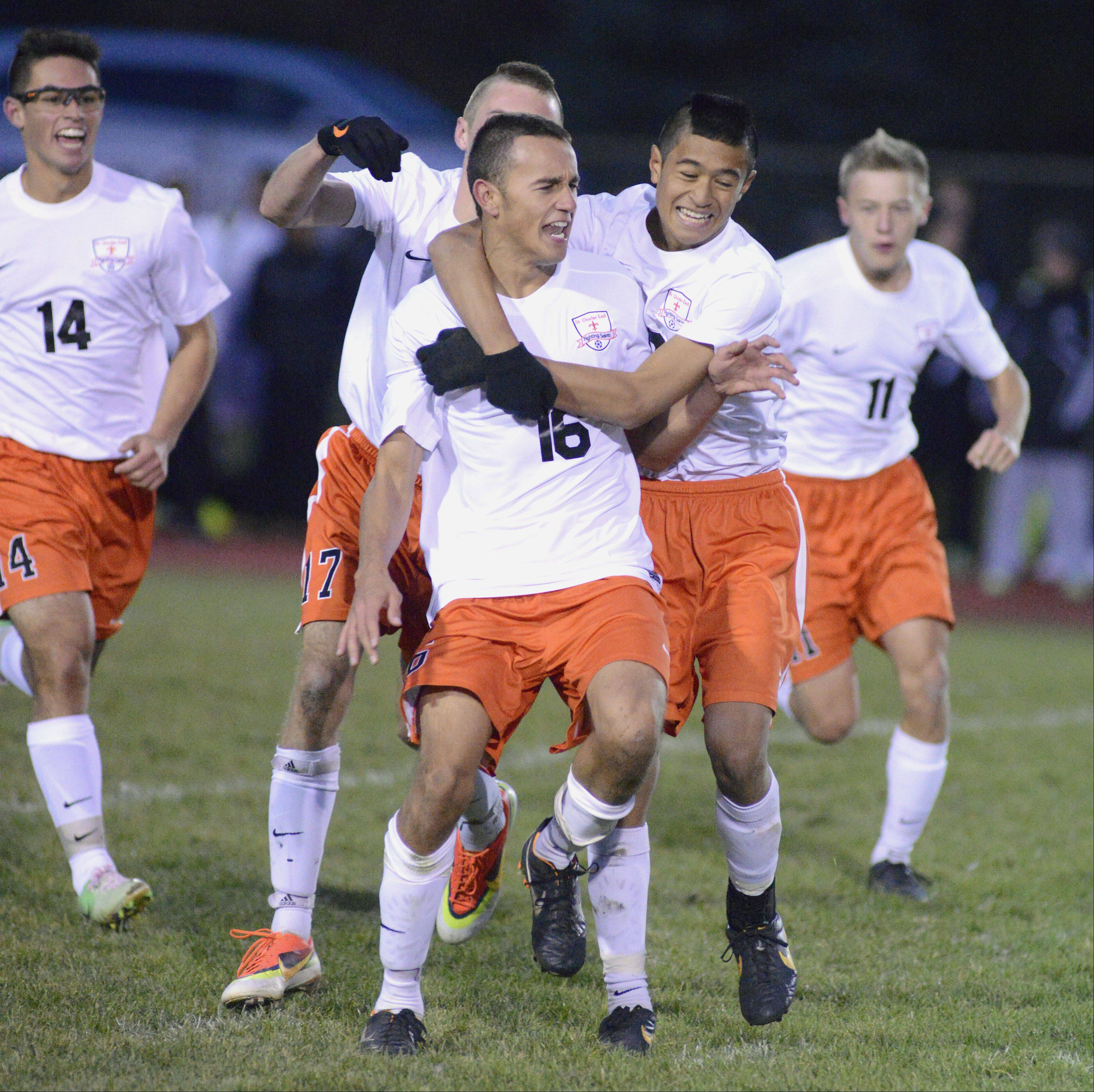 St. Charles East's Jordan Moore (16) gets a hug from teammate Zach Manibog after scoring the second goal for the Saints in the second half on Wednesday, October 23. Manibog scored the first goal of the game.