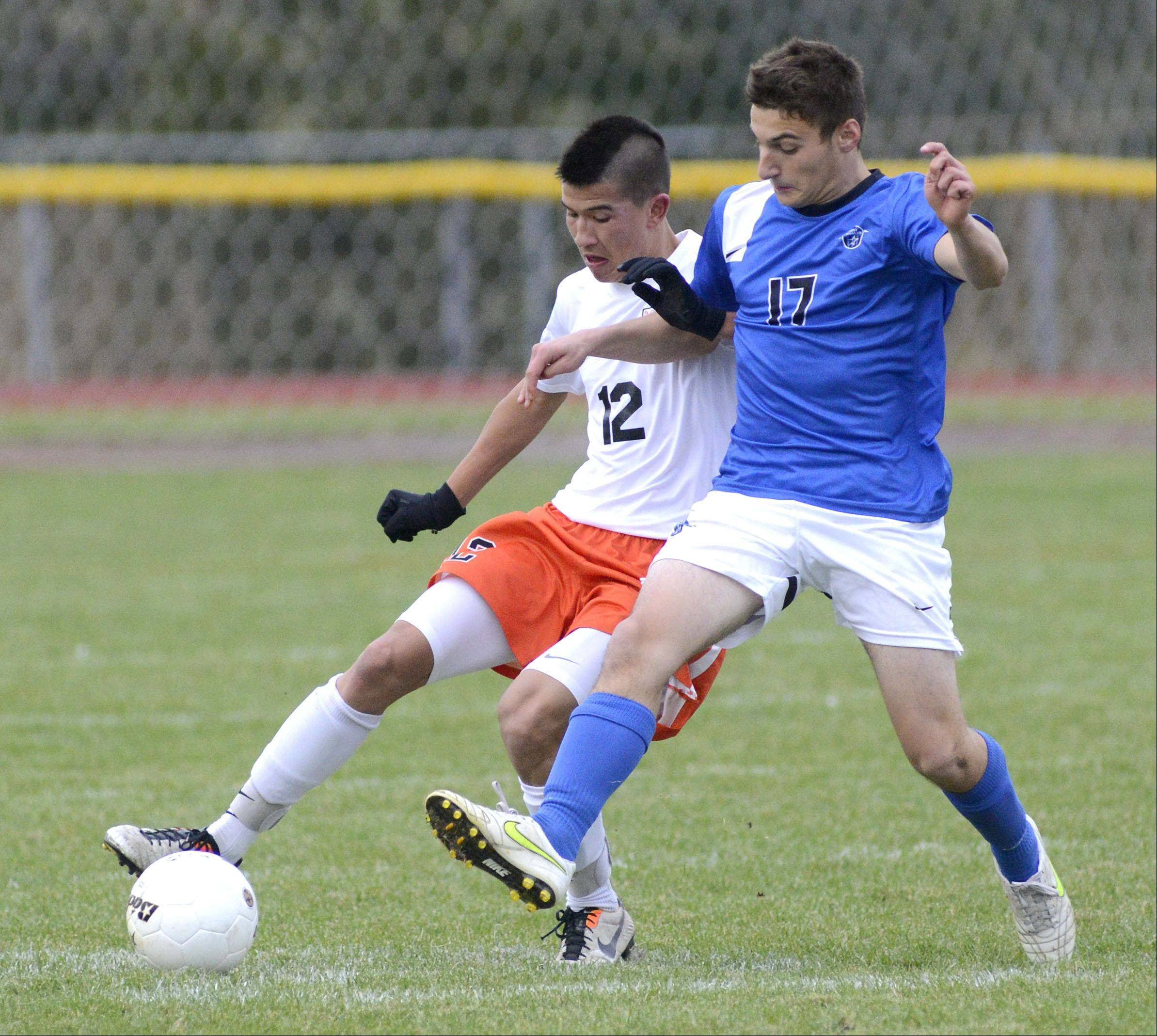 St. Charles East's Brandon Villanueva and St. Charles North's Matt Picinich battle for the ball in the first half on Wednesday, October 23.
