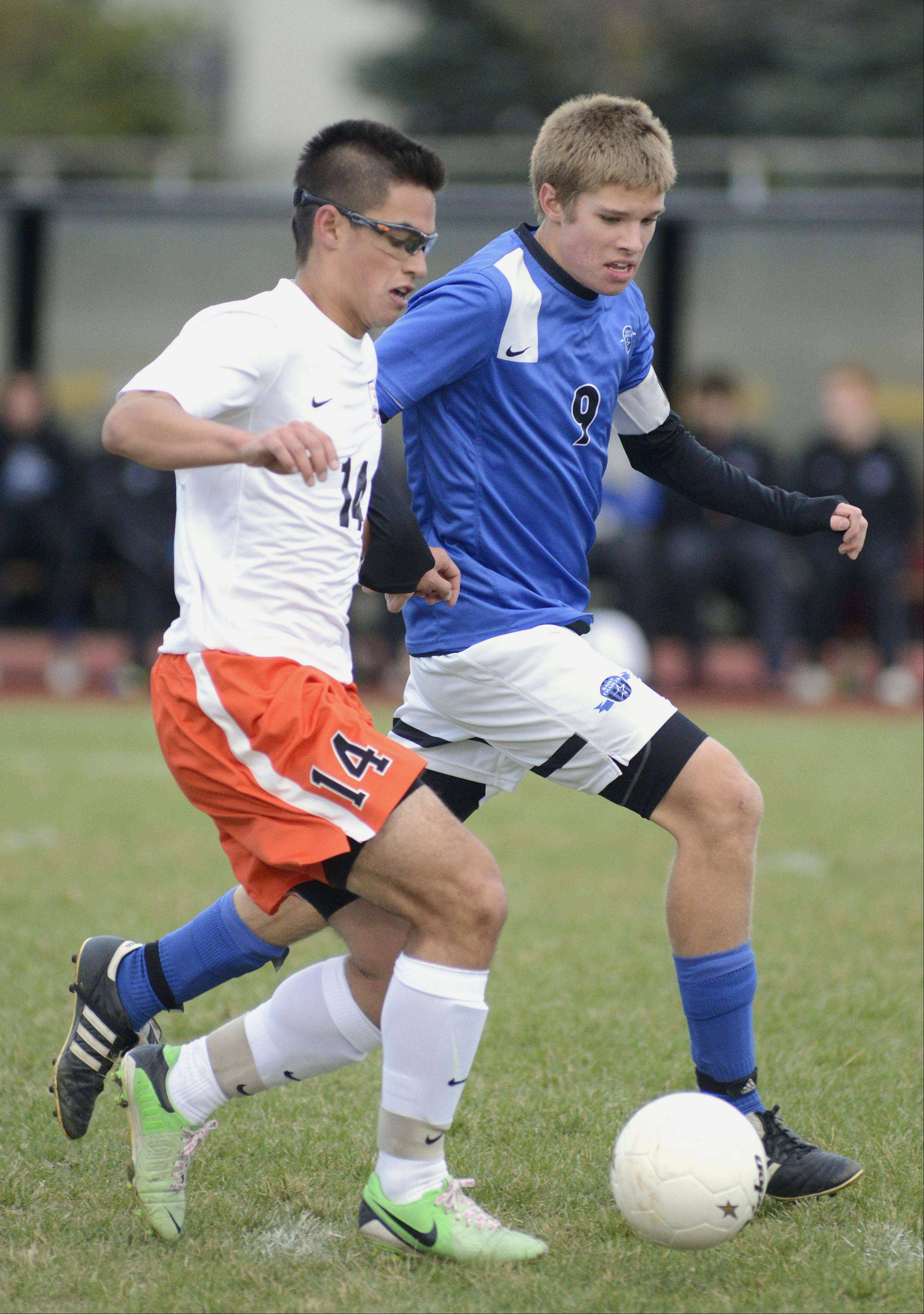 St. Charles East's Zach Manibog and St. Charles North's Brad Johnson fight for the ball in the first half on Wednesday, October 23.