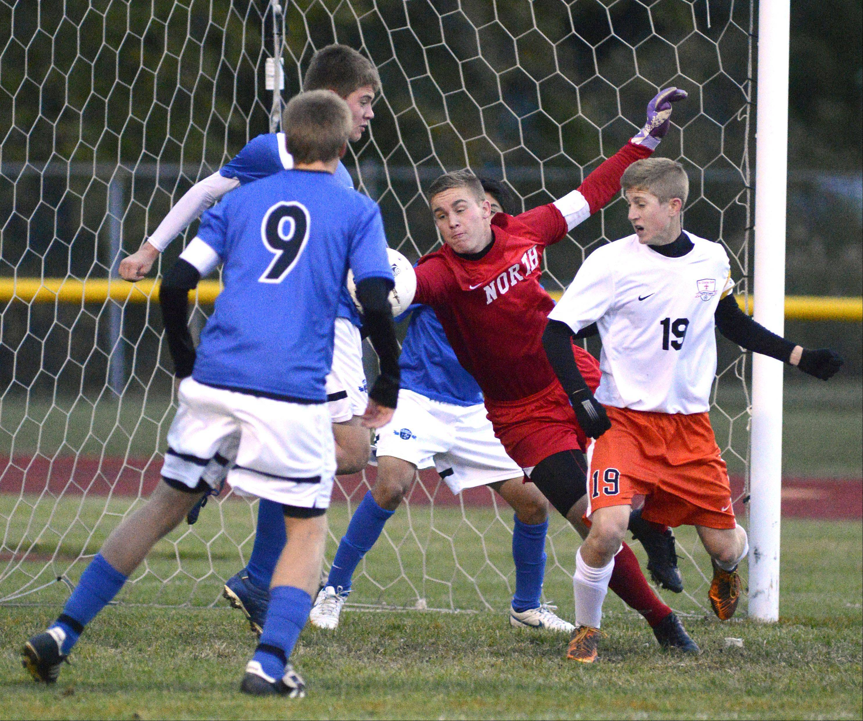 St. Charles North goalie Billy Larsen leaps to keep the ball out of the net with St. Charles East's Andrew Shone on right in the second half on Wednesday, October 23.