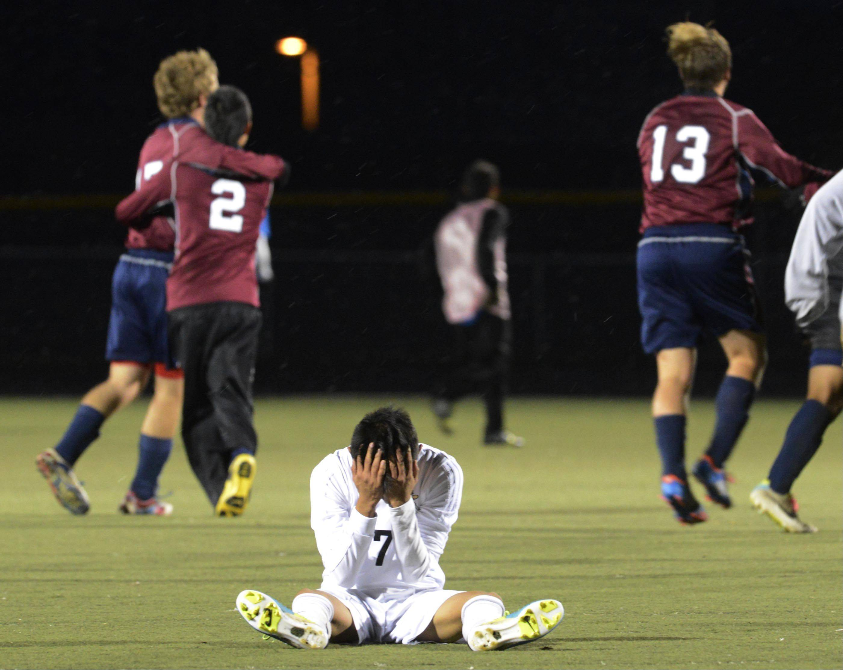 John Starks/jstarks@dailyherald.comStreamwood's Edwin Rueda holds his head as South Elgin celebrates their 2-1 win Wednesday at Millennium Field in Streamwood.