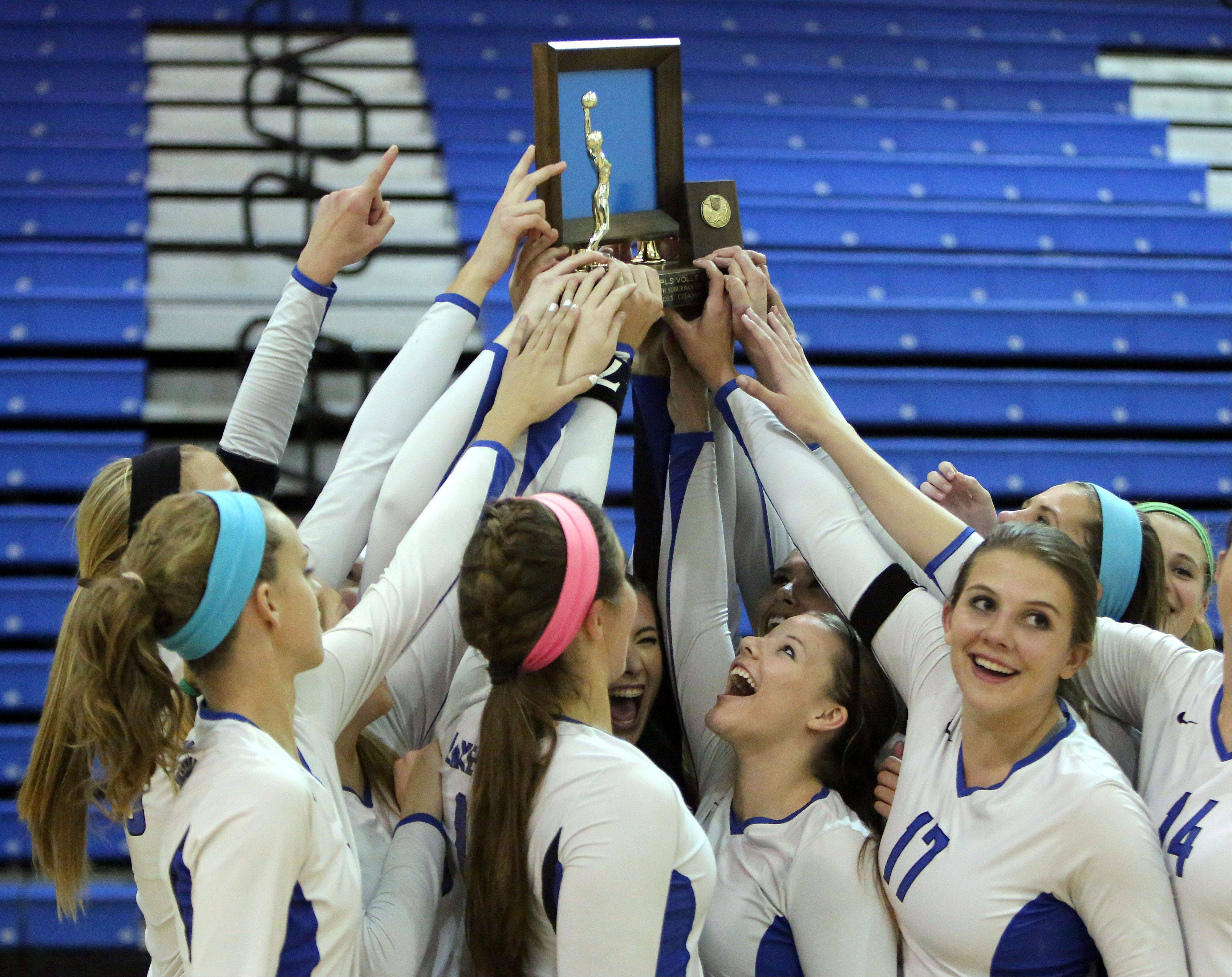 Lake Zurich celebrates with the NSC Trophy Wednesday night at Lakes High School.