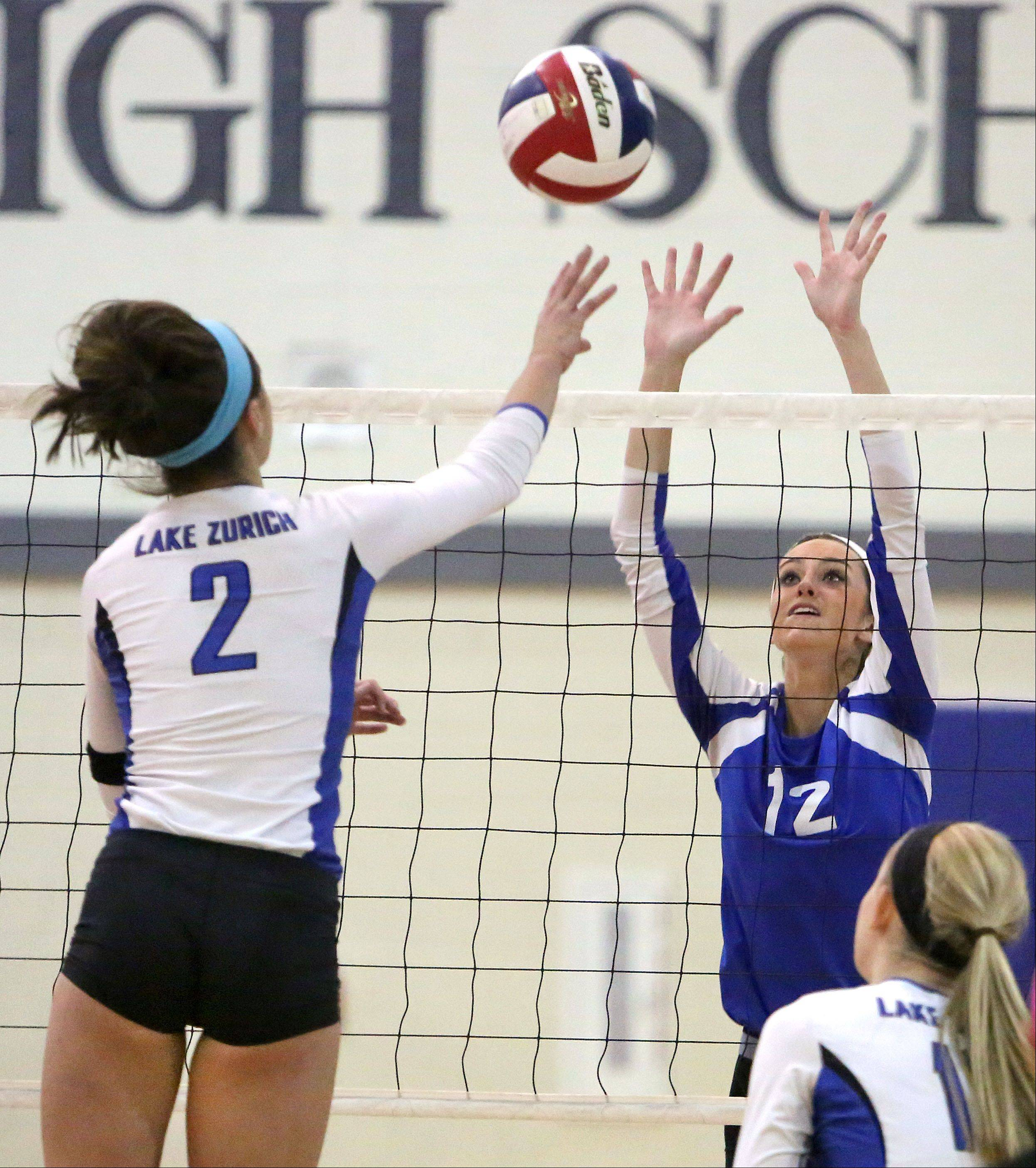 Lake Zurich's Mickenzie Andrews, left, and Lakes' Haley Halberg meet at the net during the NSC title game Wednesday night at Lakes High School.