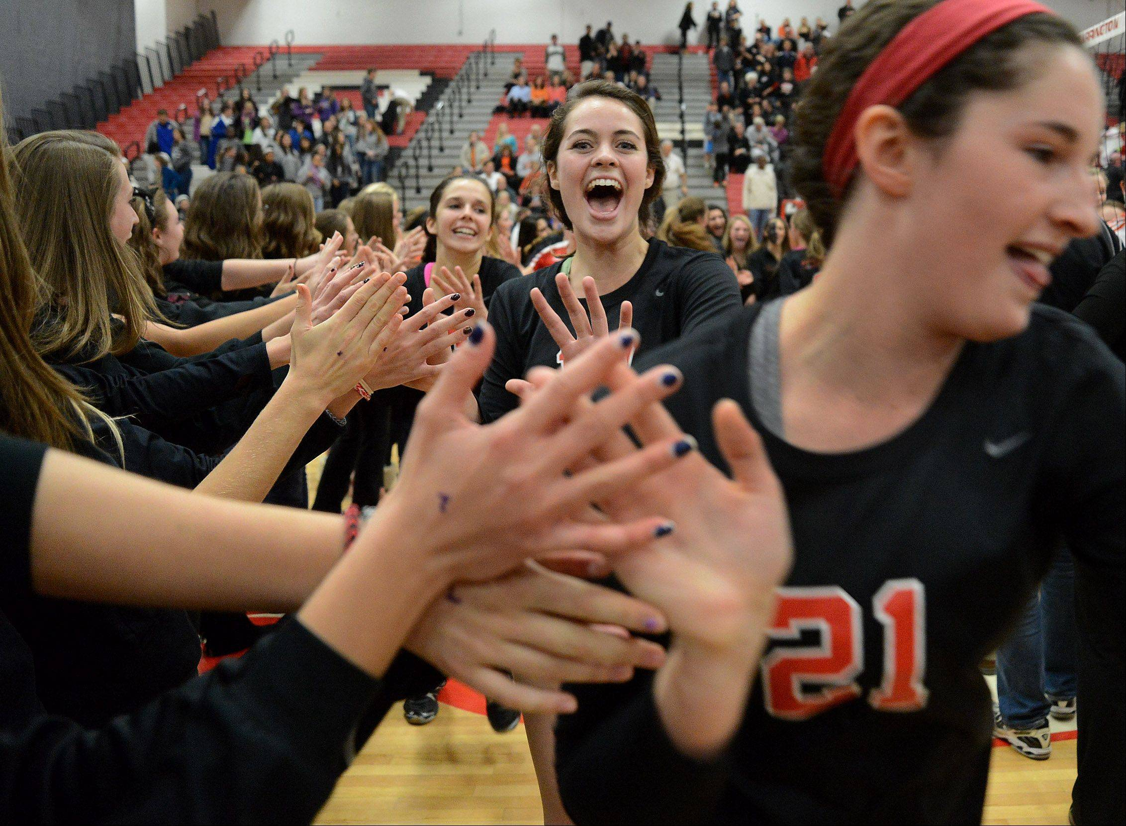 Ellie Lauderback, center, and Jess Terrill, right, celebrate with teammates after beating Hersey in Mid-Suburban League girls volleyball championship matchup.