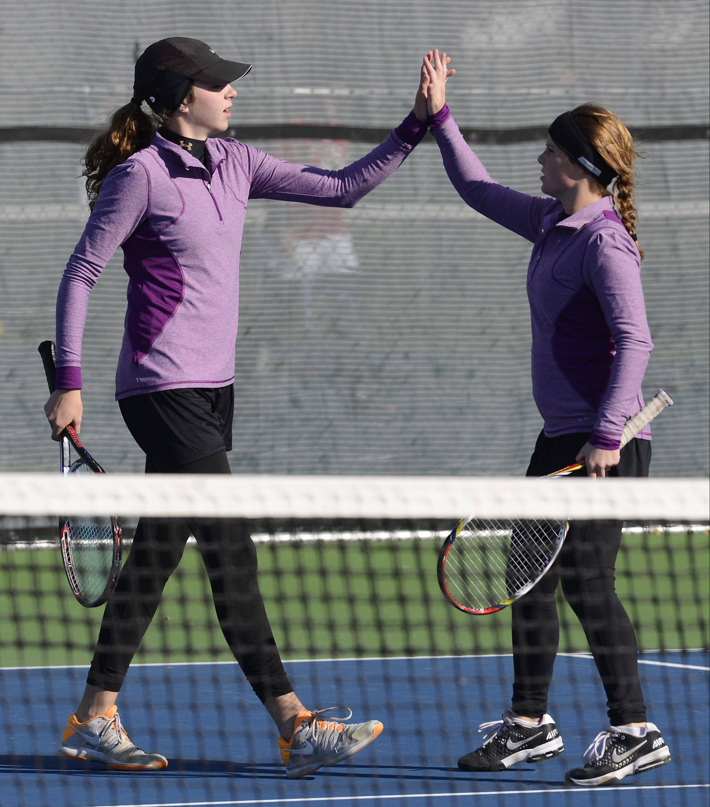 Batavia doubles players Brooke Lefevre, left, and Sydnee Unterberg high-five after a point against Libertyville during the state tennis preliminaries at Prospect Thursday.