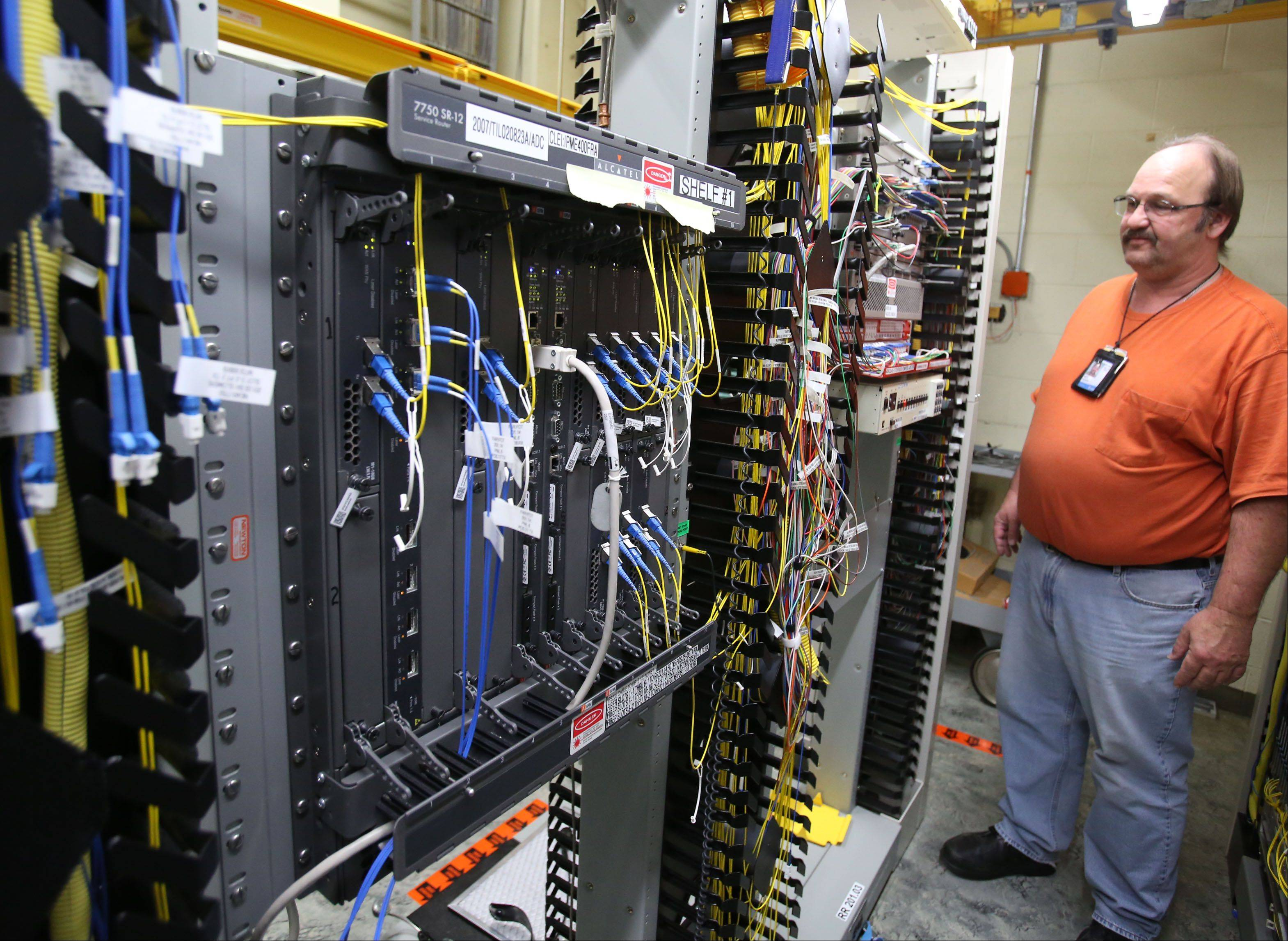 Guy Huttberg, a technician at AT&T Central Office in Barrington, is with new technology used for Internet protocol-based voice and video data on Thursday.