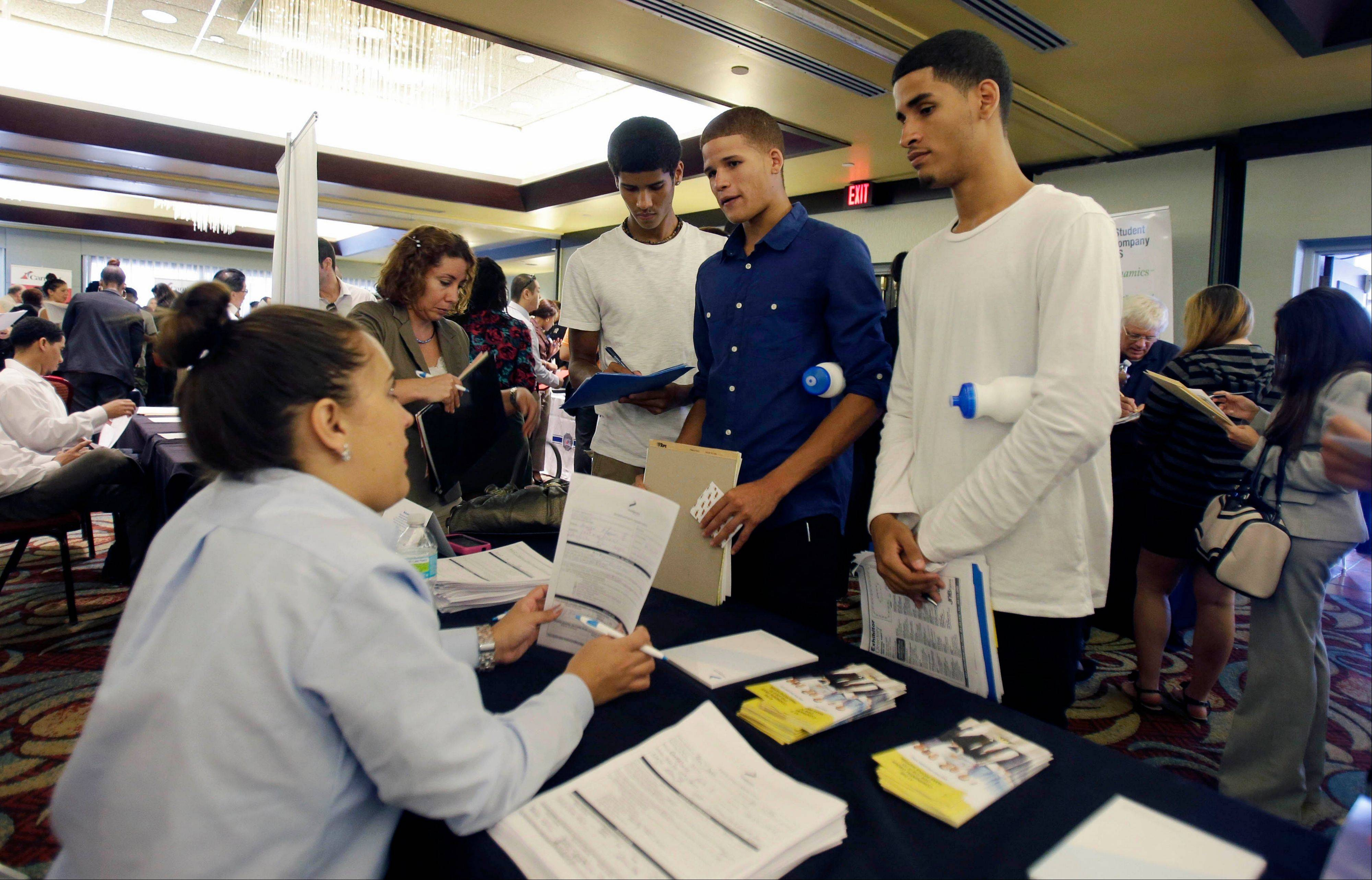Job seekers Emilio Ferrer, Brian Ferrer, center, and Jonathan, right, of Hollywood, Fla., talk to a FirstService representative at a job fair in Miami Lakes, Fla.