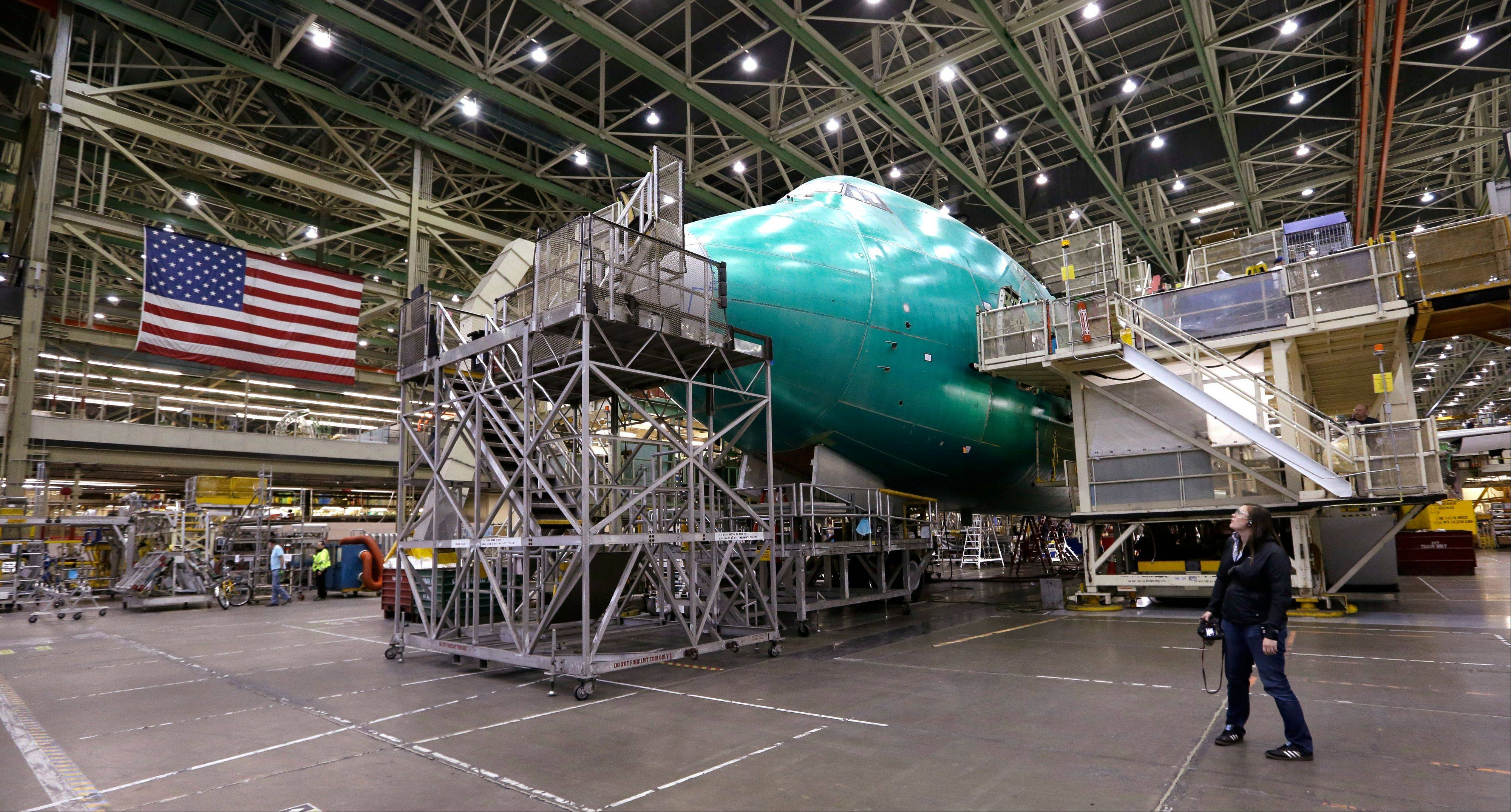 A visitor looks up at a Boeing 747 jet being assembled at the company's production plant in Everett, Wash.