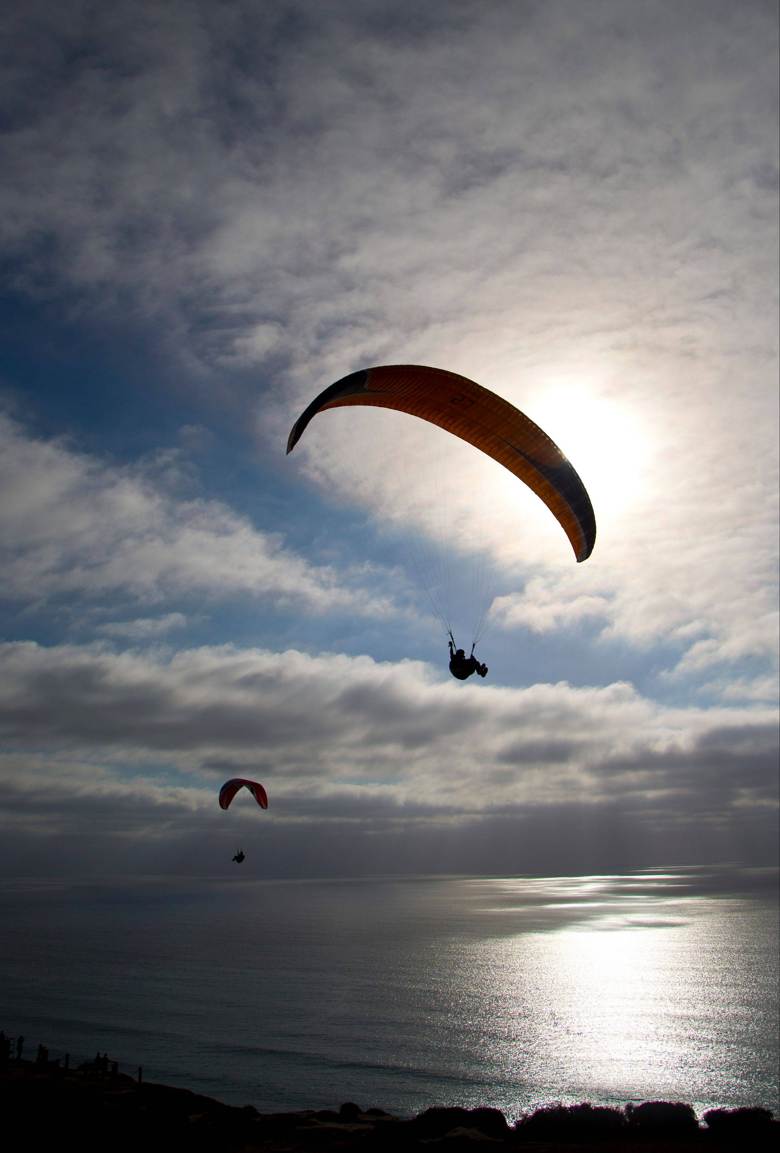 Gliders sail past the setting sun at the glider port, which is open to the public and provides breathtaking views of the Southern California coast in San Diego.