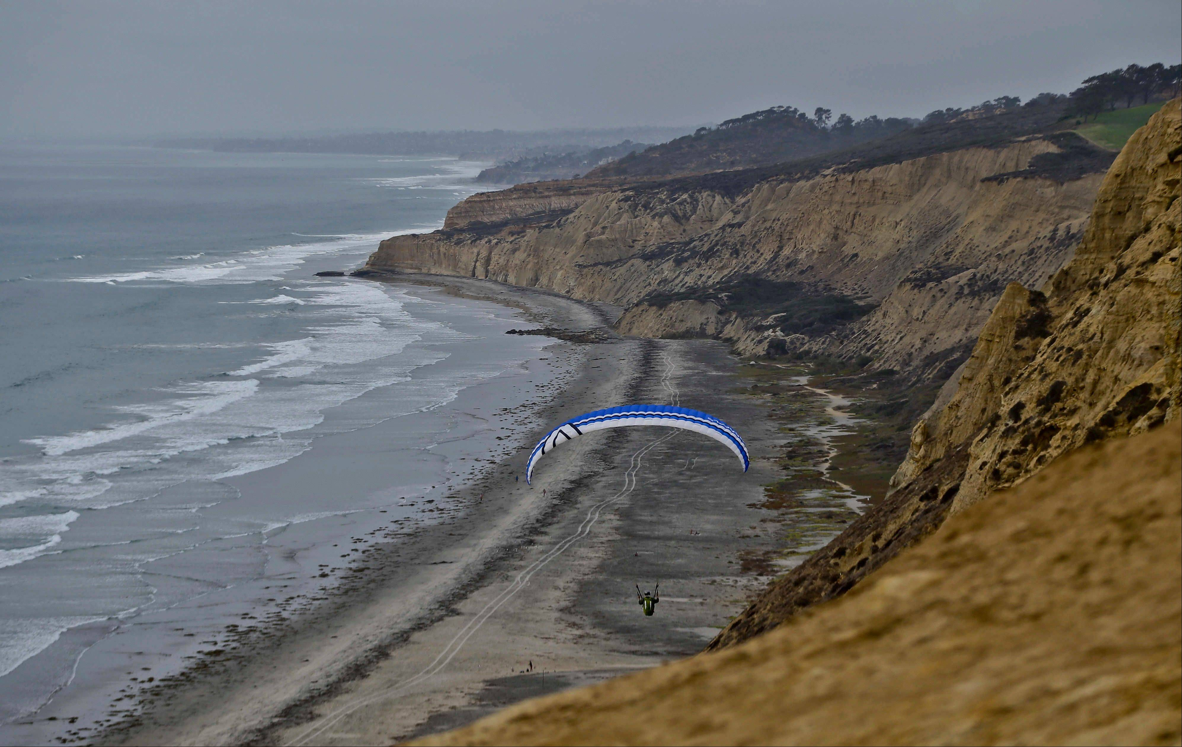 A lone glider sails north over the rugged cliffs of the Southern California coast in San Diego. The glider port is open to the public and offers fantastic views and refreshments.