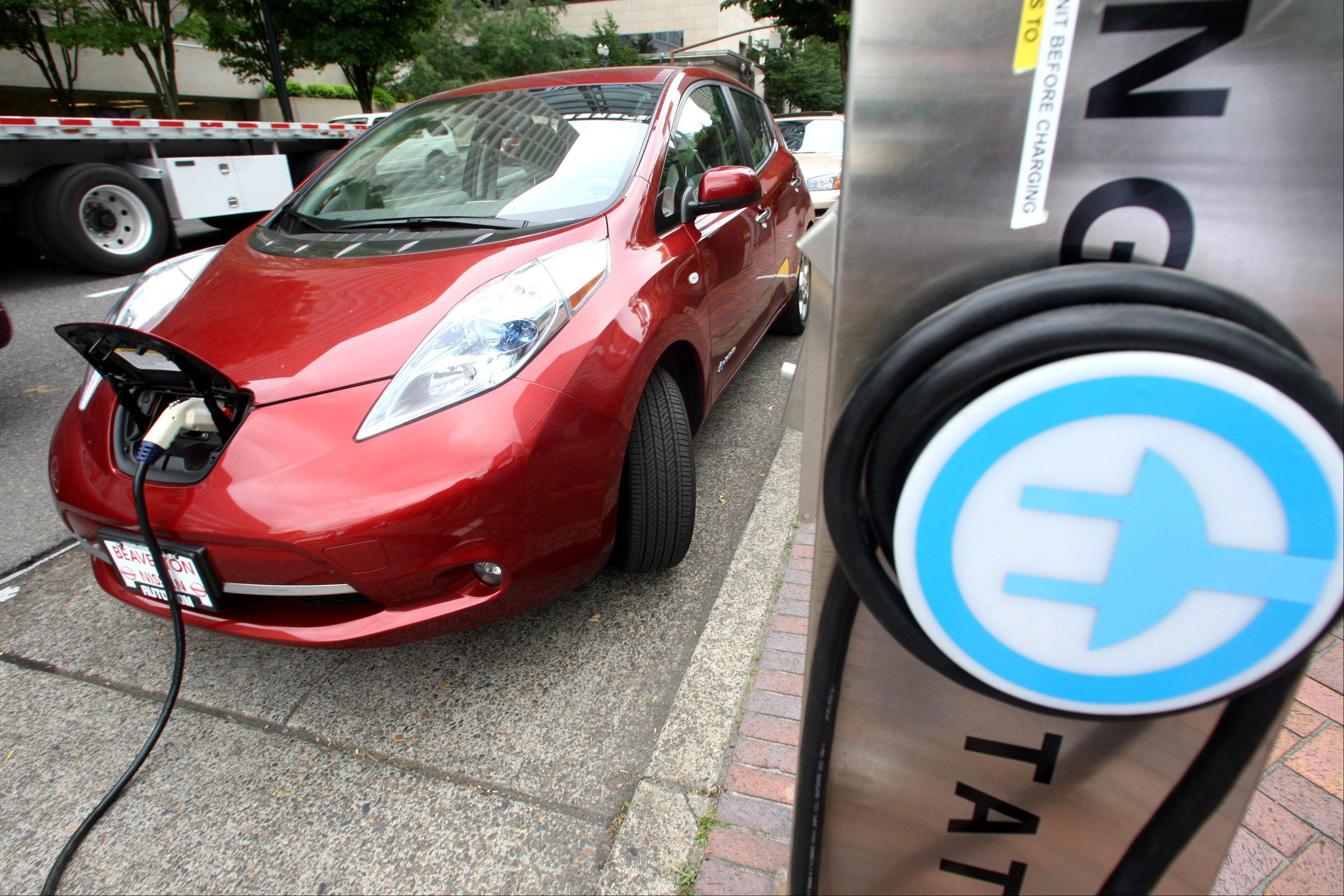 A Nissan Leaf charges at an electric vehicle charging station in Portland, Ore. The governors of eight states, including California and New York, pledged Thursday to get 3.3 million zero-emission vehicles on roadways by 2025 in an effort to curb greenhouse gas pollution.