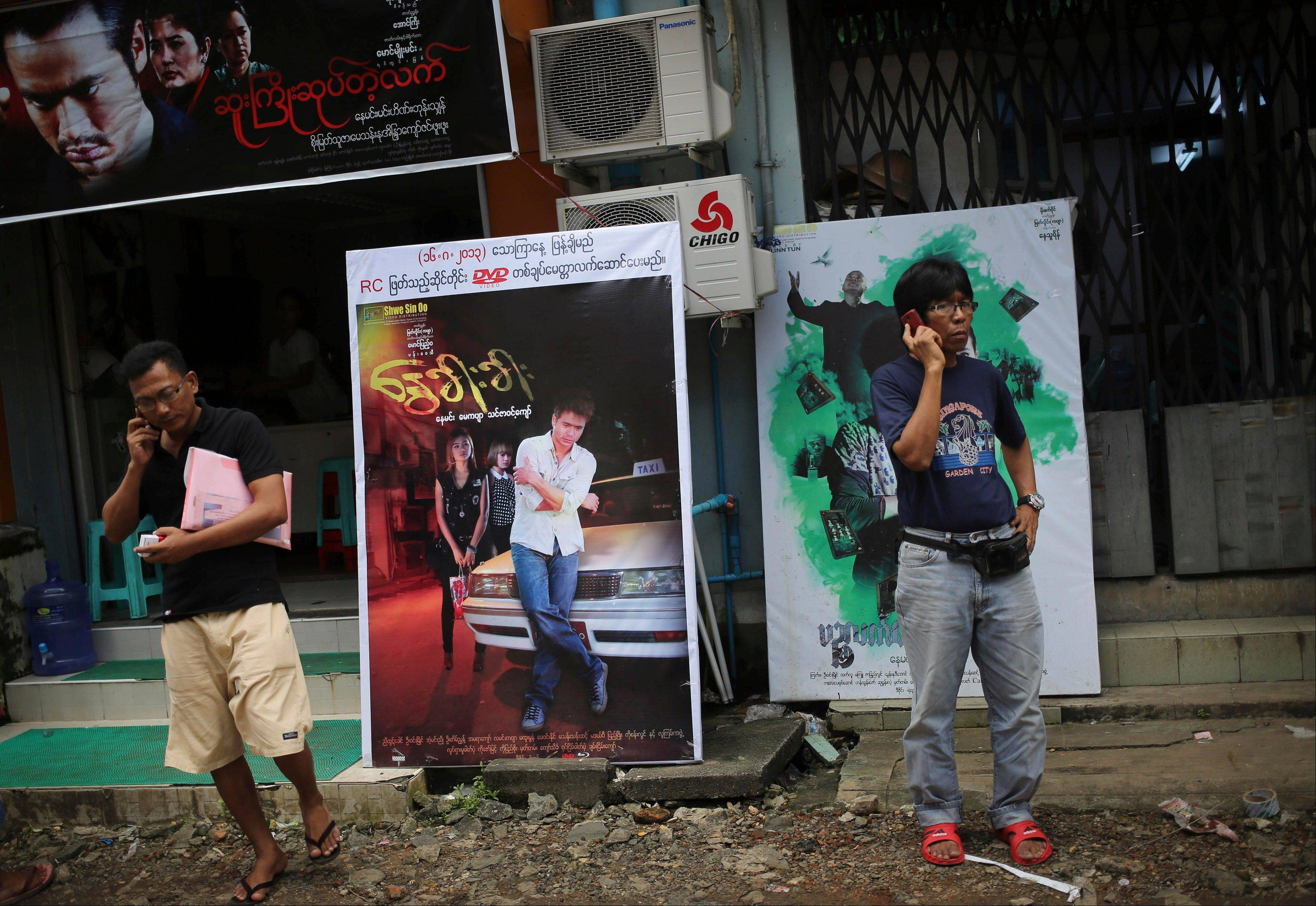 Burmese people use their cell phones amidst the tightly packed enclave of video production houses, movie-poster design studios and worse-for-wear apartment buildings that serves as the tattered ground zero of the Burmese movie industry, in downtown Yangon, Myanmar.