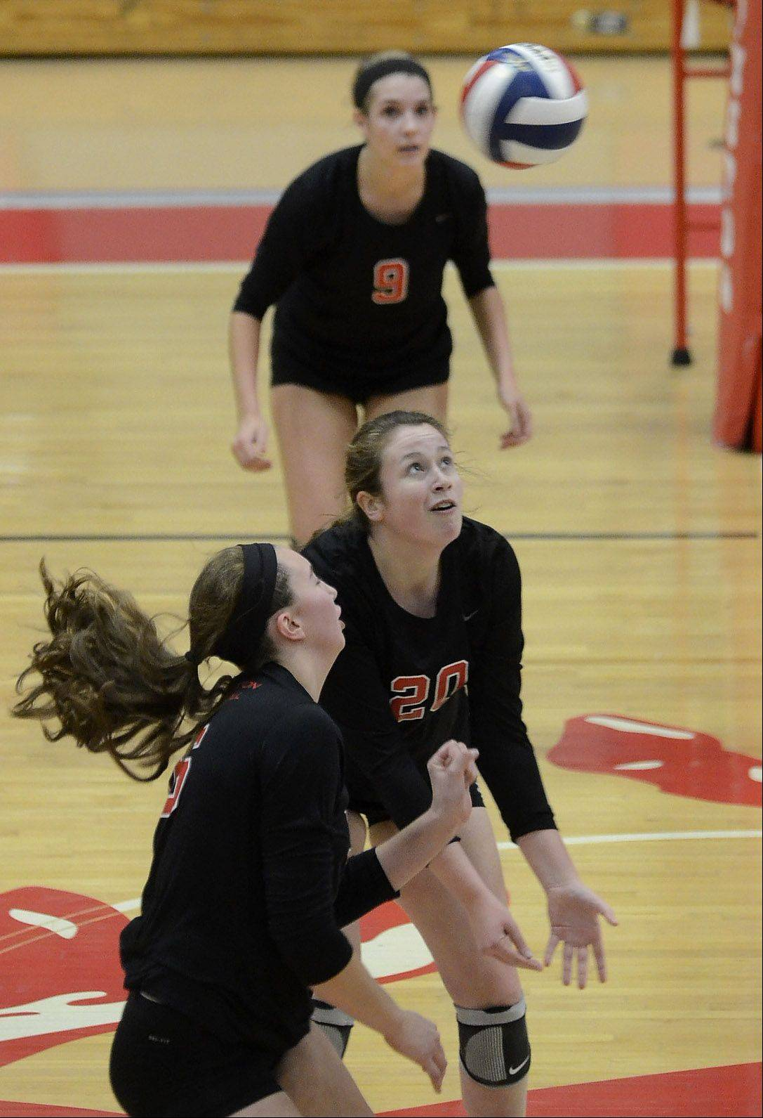 Barrington's Emily Watkins, top, Sarah Berggren, middle, and Megan Talbot, bottom, converge on a ball against Hersey in Thursday's Mid-Suburban League girls volleyball championship matchup.