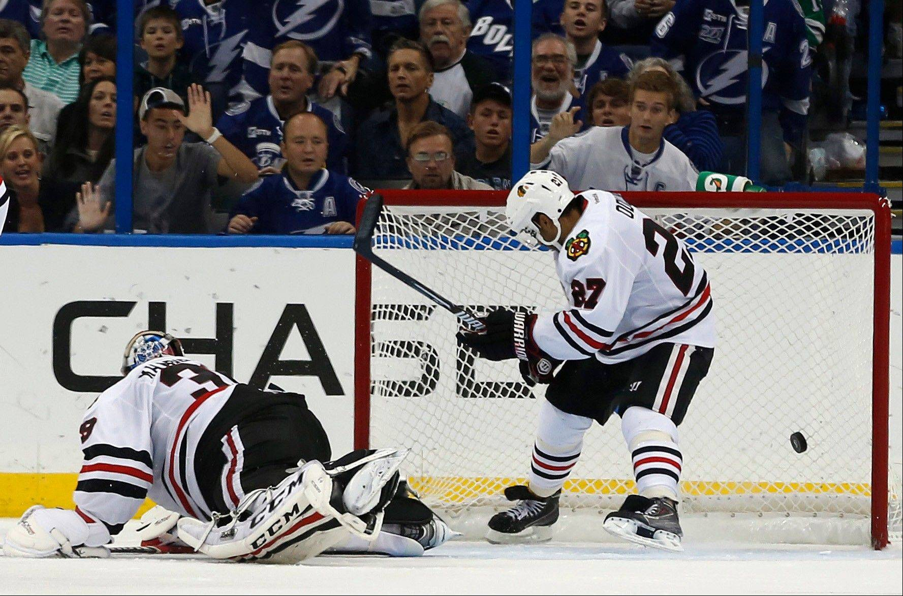 Blackhawks goalie Nikolai Khabibulin (39) cannot stop a backhand goal from Tampa Bay Lightning right wing Martin St. Louis as Blackhawks defenseman Johnny Oduya (27) tries to guard the goal during the sudden death overtime period of a game Thursdayin Tampa, Fla.