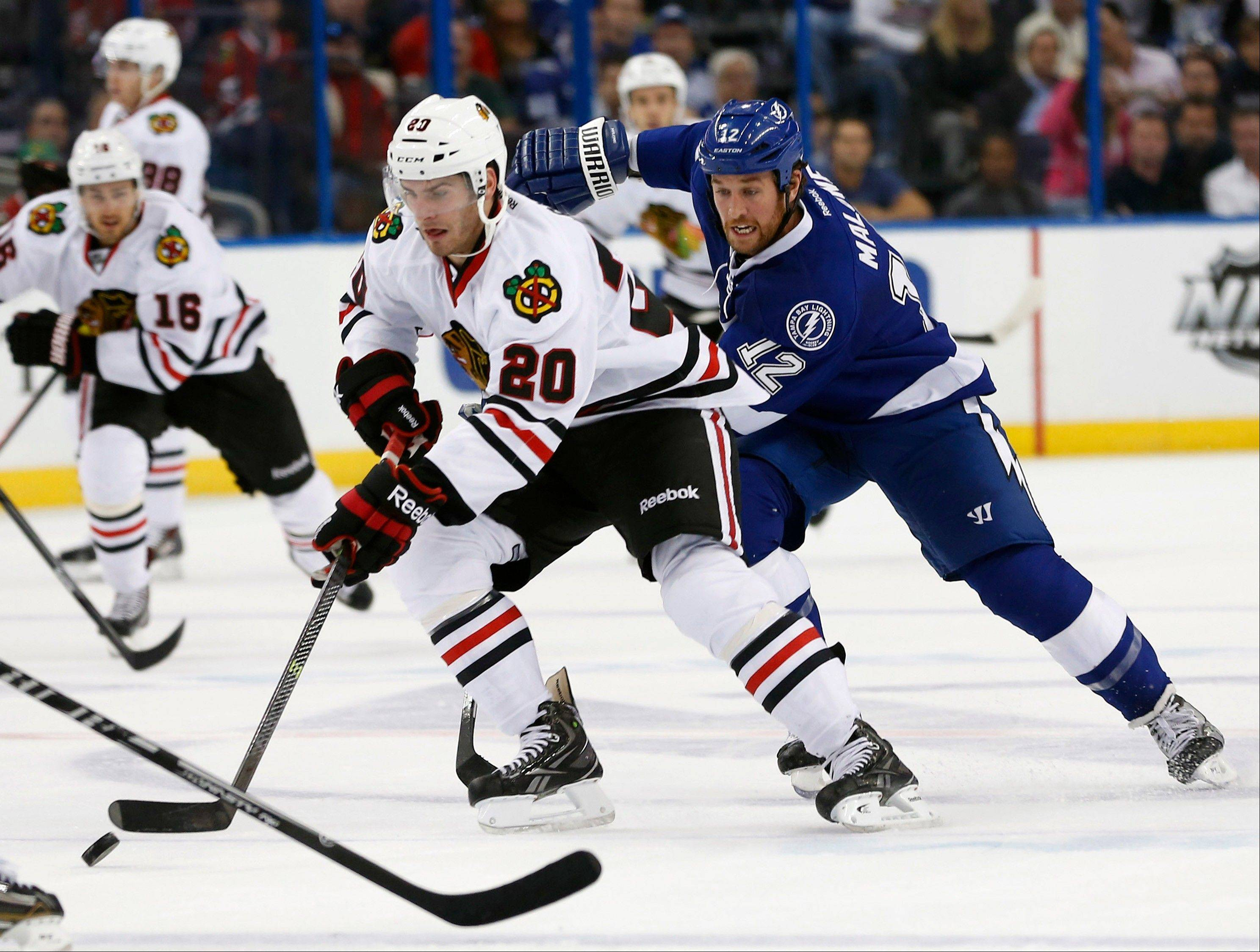 Tampa Bay Lightning left wing Ryan Malone (12) tries to catch Blackhawks left wing Brandon Saad (20) during the first period of a game on Thursday in Tampa, Fla.
