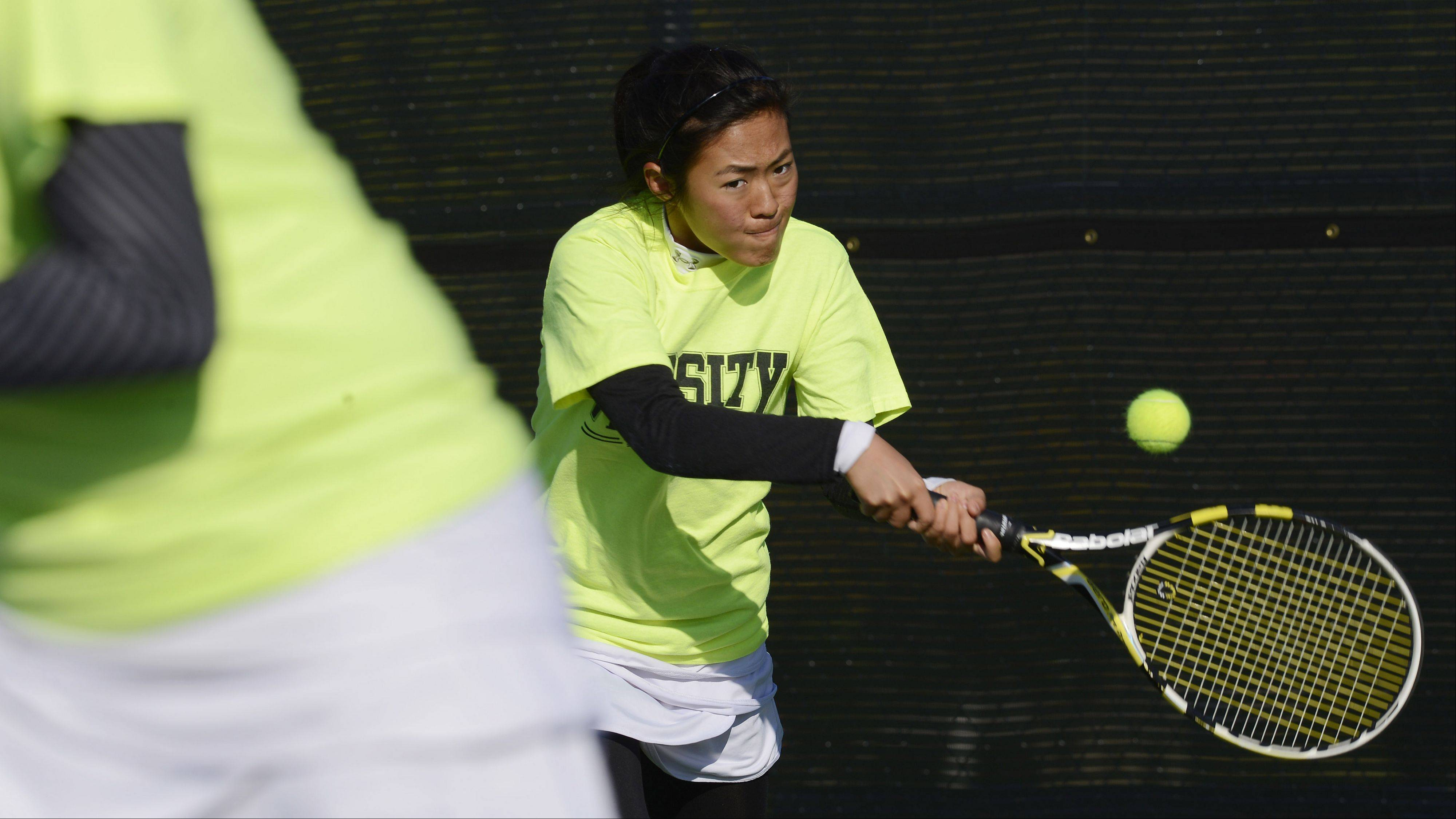 Naperville North's Julia Li returns a serve as doubles partner Jessica Hu stands ready at the net during the girls state tennis preliminaries at Prospect High School Thursday.