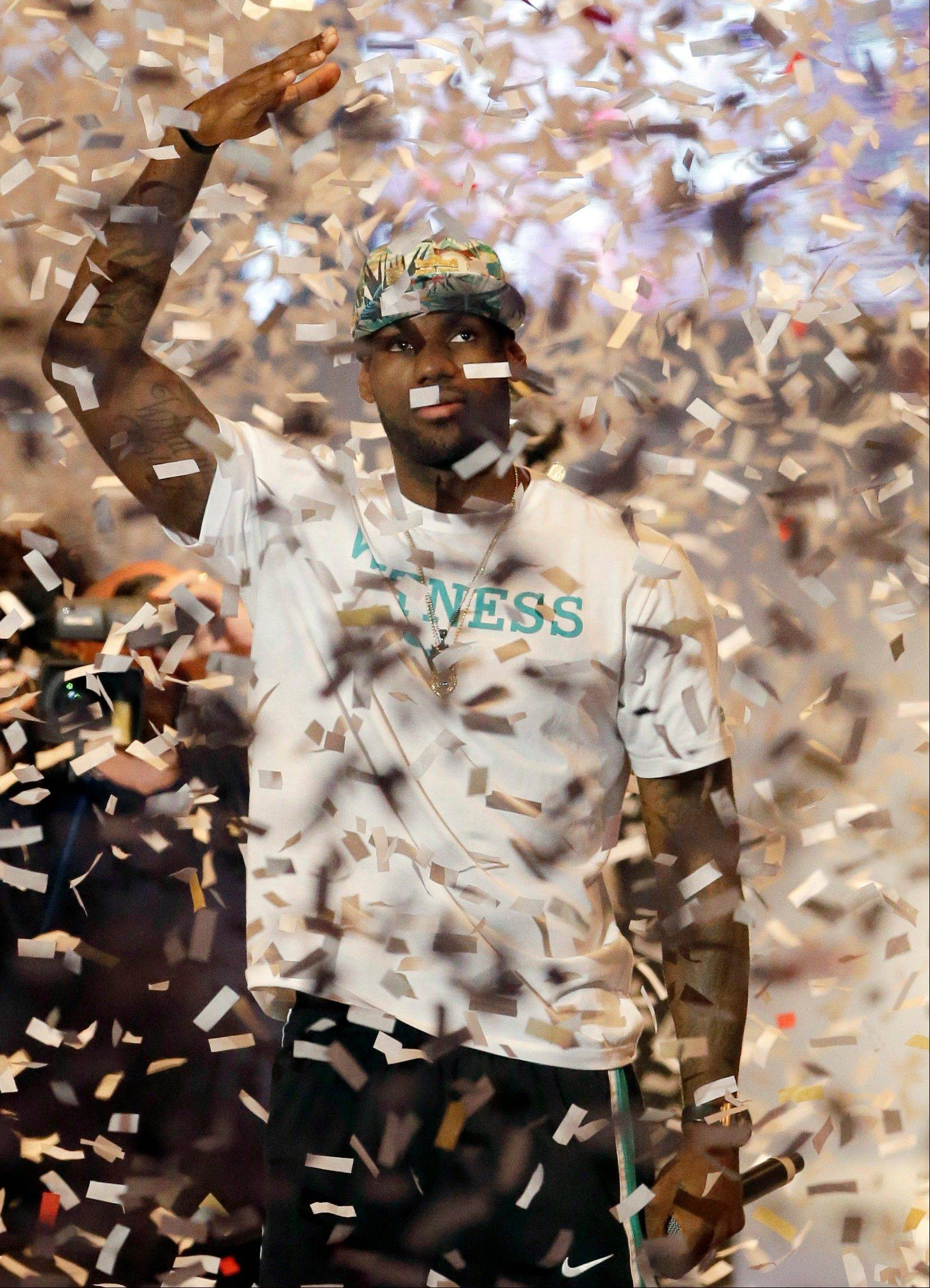 Miami Heat forward LeBron James, here celebrating his team's second straight NBA title, will begin his quest for a three-peat when the season opens Tuesday against the Bulls and Derrick Rose. The Heat defeated the San Antonio Spurs 95-88 in Game 7 to win last season's title.