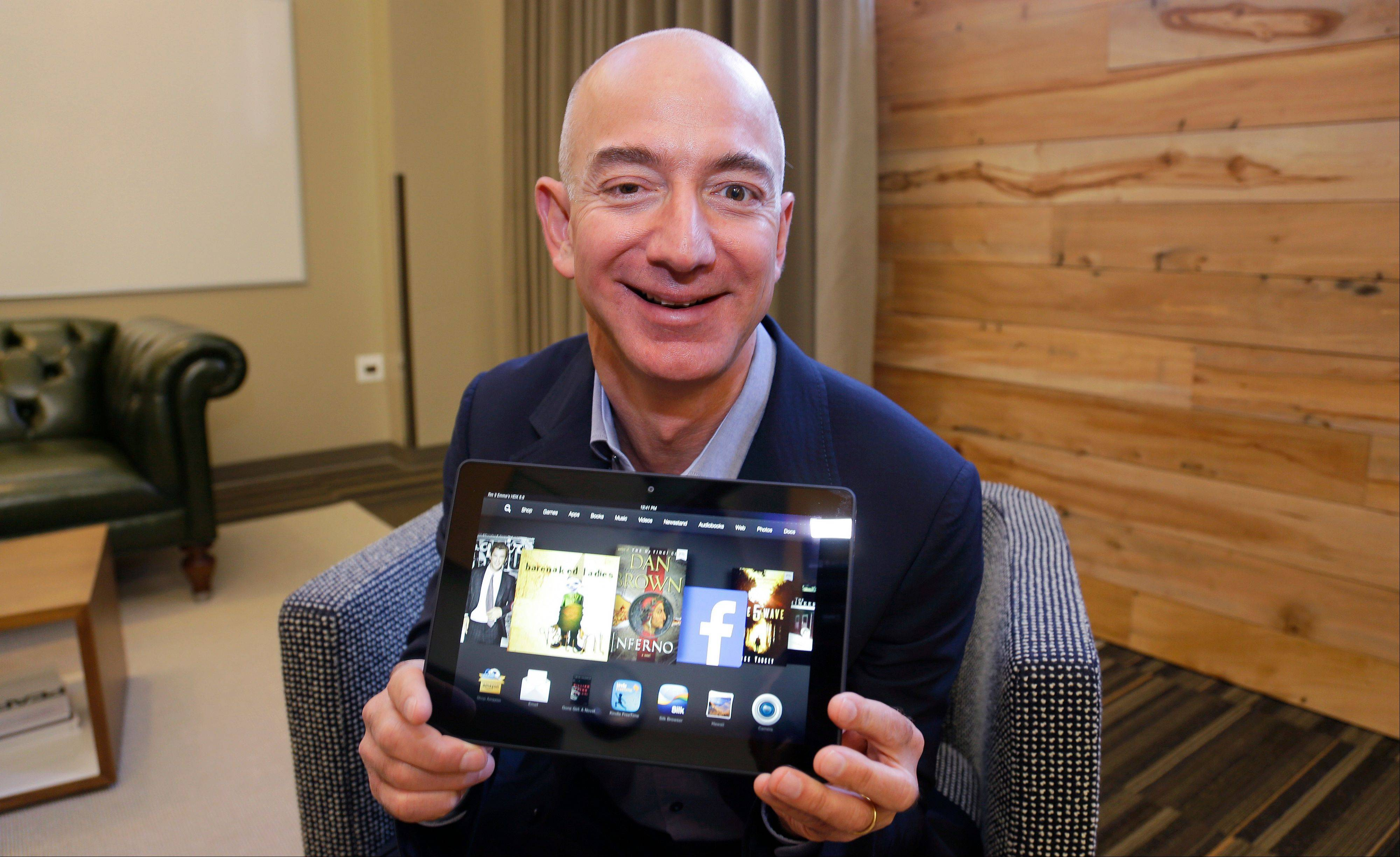 Jeff Bezos, CEO of Amazon.com, holds the 8.9-inch version of the new Amazon Kindle HDX tablet computer in Seattle. Amazon.com's revenue rose more than Wall Street expected in its fiscal third quarter, but the online retailer posted another loss due to ongoing investments in its business.
