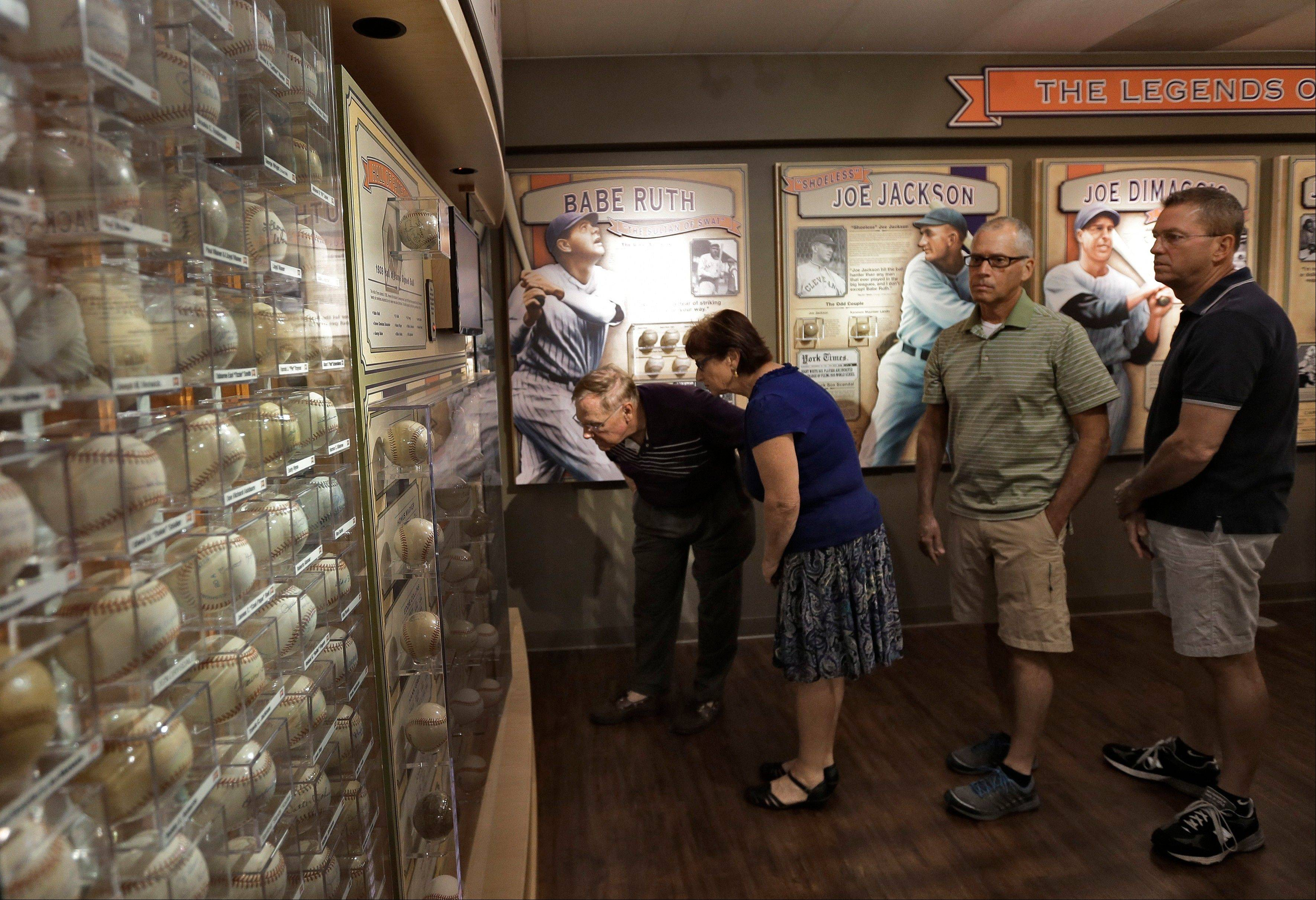 Visitors to the St. Petersburg Museum of History view some of Dennis Schrader's autographed baseballs Tuesday in St. Petersburg, Fla. Schrader now has more than 4,600 signed baseballs, and that obsession is now on display at the museum.