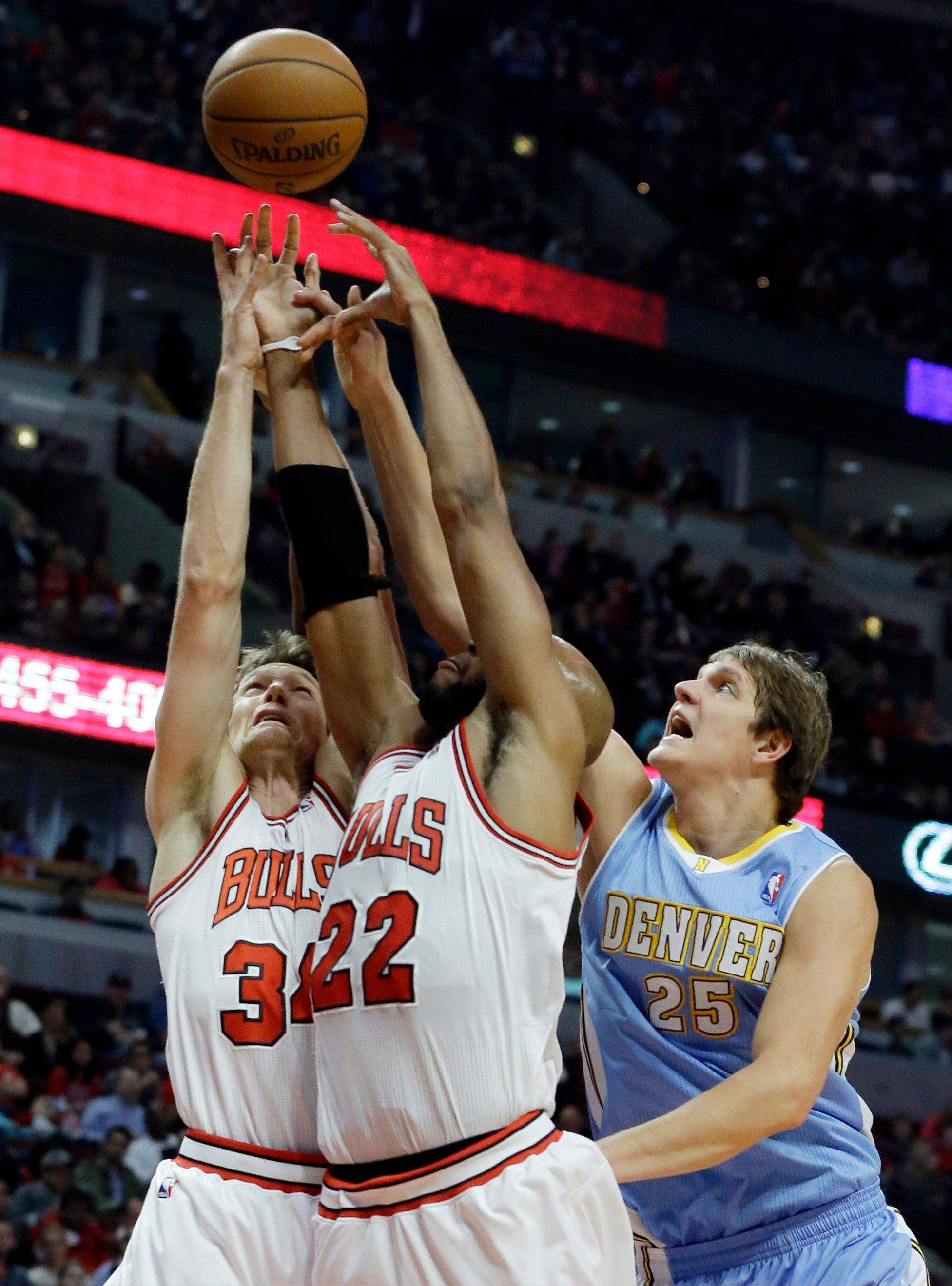 Denver Nuggets center Timofey Mozgov (25) battle for a rebound against Chicago Bulls guard Mike Dunleavy, left, and Taj Gibson during the first half of an NBA preseason basketball game in Chicago on Friday, Oct. 25, 2013. (AP Photo/Nam Y. Huh)