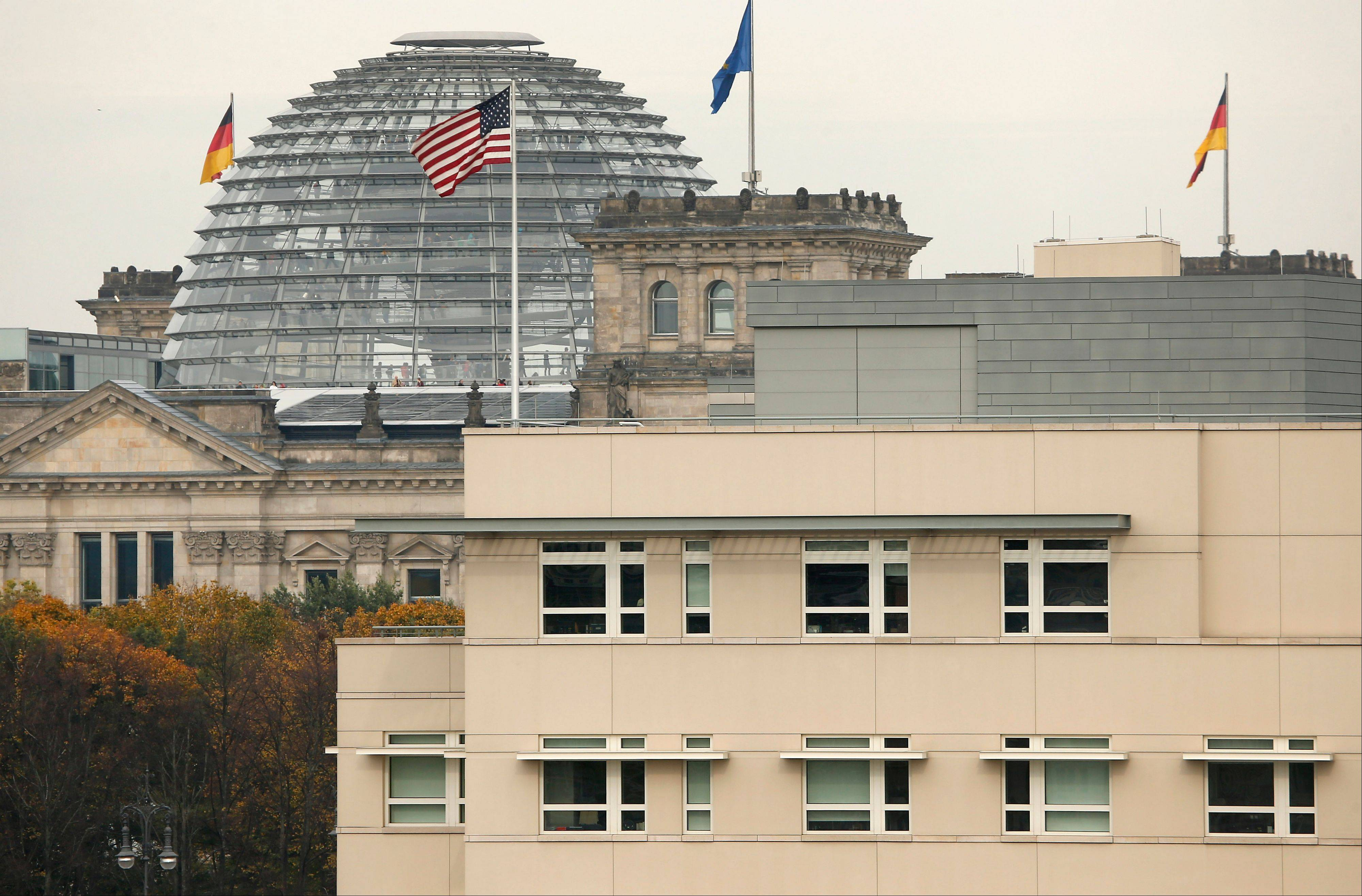 The American flag flies on top of the U.S. embassy in front of the Reichstag building that houses the German Parliament in Berlin.