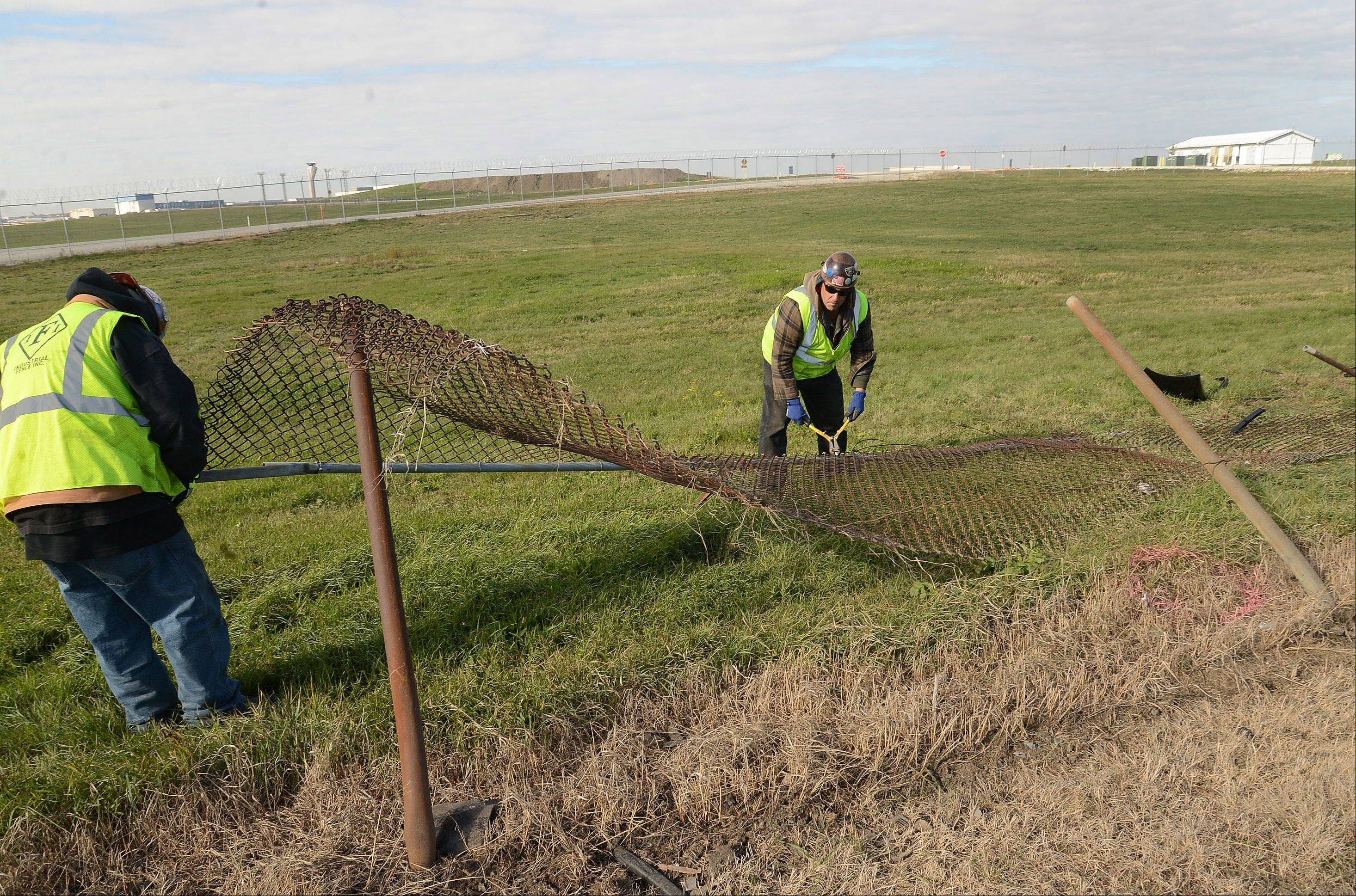 Ornamental iron workers Gerardo Campos, left, and Dan Morton begin to repair the fencing on Higgins Road between Mannheim and Touhy.