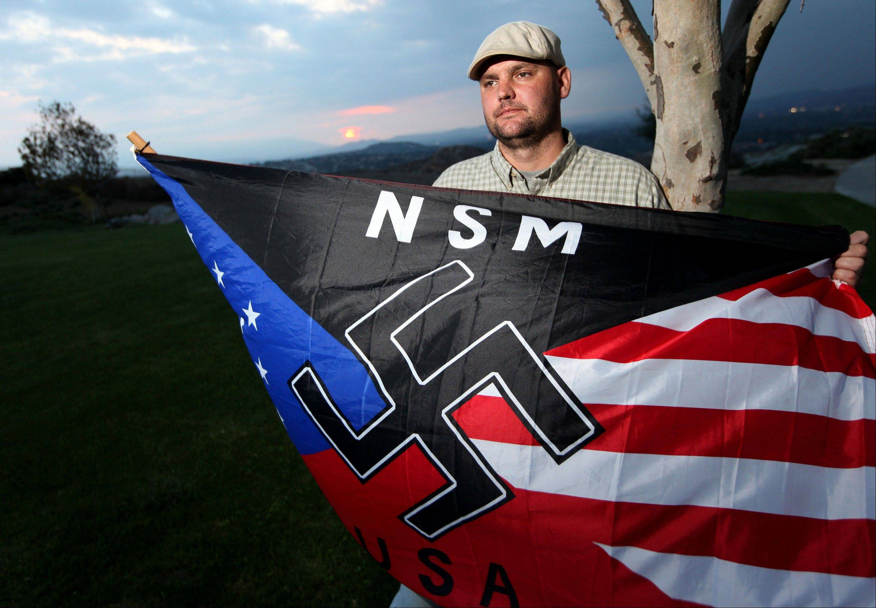 Jeff Hall, who was killed by his son, holds a Neo Nazi flag while standing at Sycamore Highlands Park near his home in Riverside, Calif. On Friday Oct. 25, 2013 a judge will to determine where Hall's son will spend his teens and, possibly, his early adult years. The judge hearing the case in Riverside County must decide not how to punish a child for second-degree murder, but how to rehabilitate someone who grew up in an abusive home.