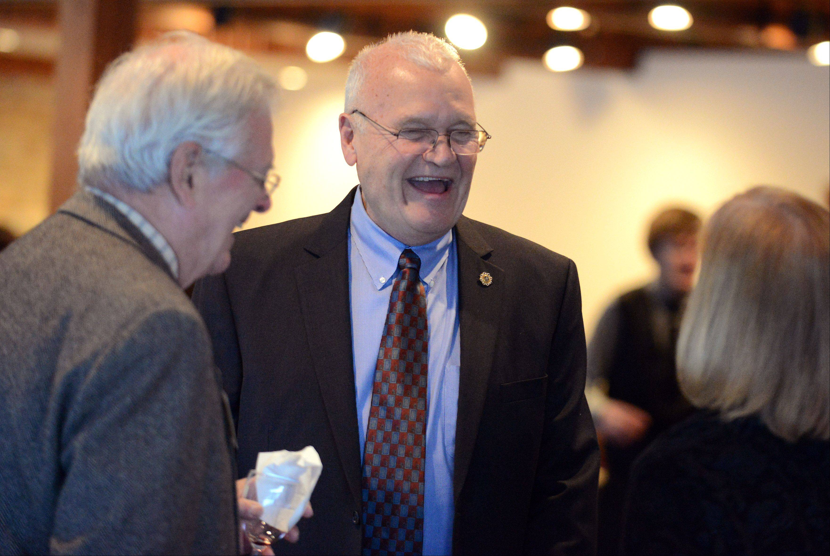 Fred Norris laughs as he is greeted by Bob and Diana MacNeille of St. Charles after being announced as the winner of the 29th annual William D. Barth Award in Geneva Thursday. The award is given by TriCity Family Services.