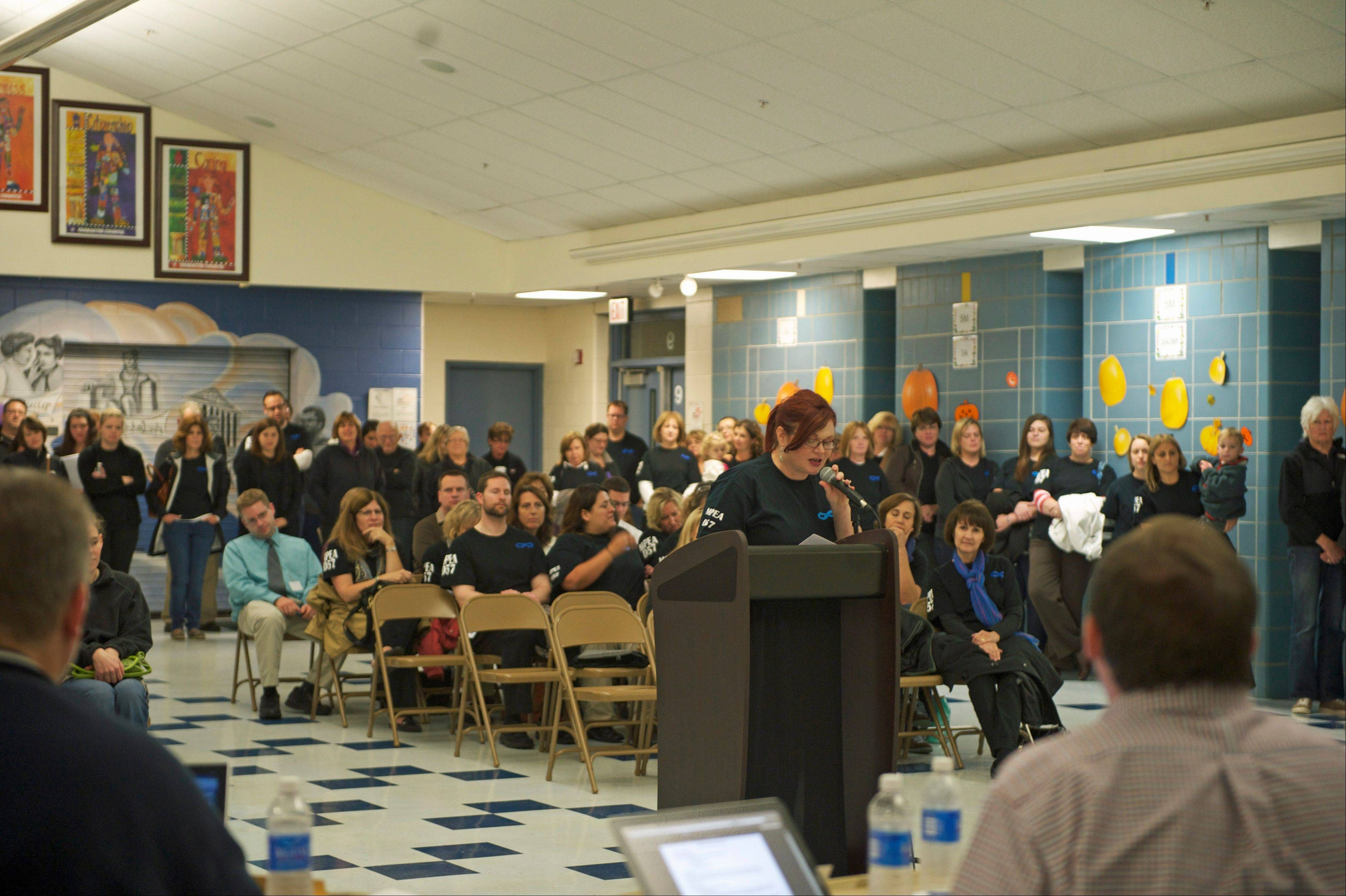 Michelle Walsh, president of the Mount Prospect Education Association, addresses the Mount Prospect Elementary District 57 school board during a recent meeting, with fellow union members behind her. The union and district have decided to ask a federal mediator to help them reach a contract agreement.